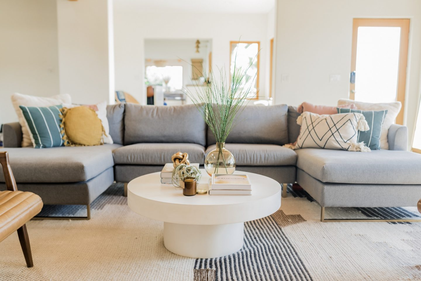 Home Remodel: Modern Family Room Reveal by popular California life and style blog, Navy Grace: image of a modern family room with a large grey sectional couch, leather arm chair and round white coffee table.