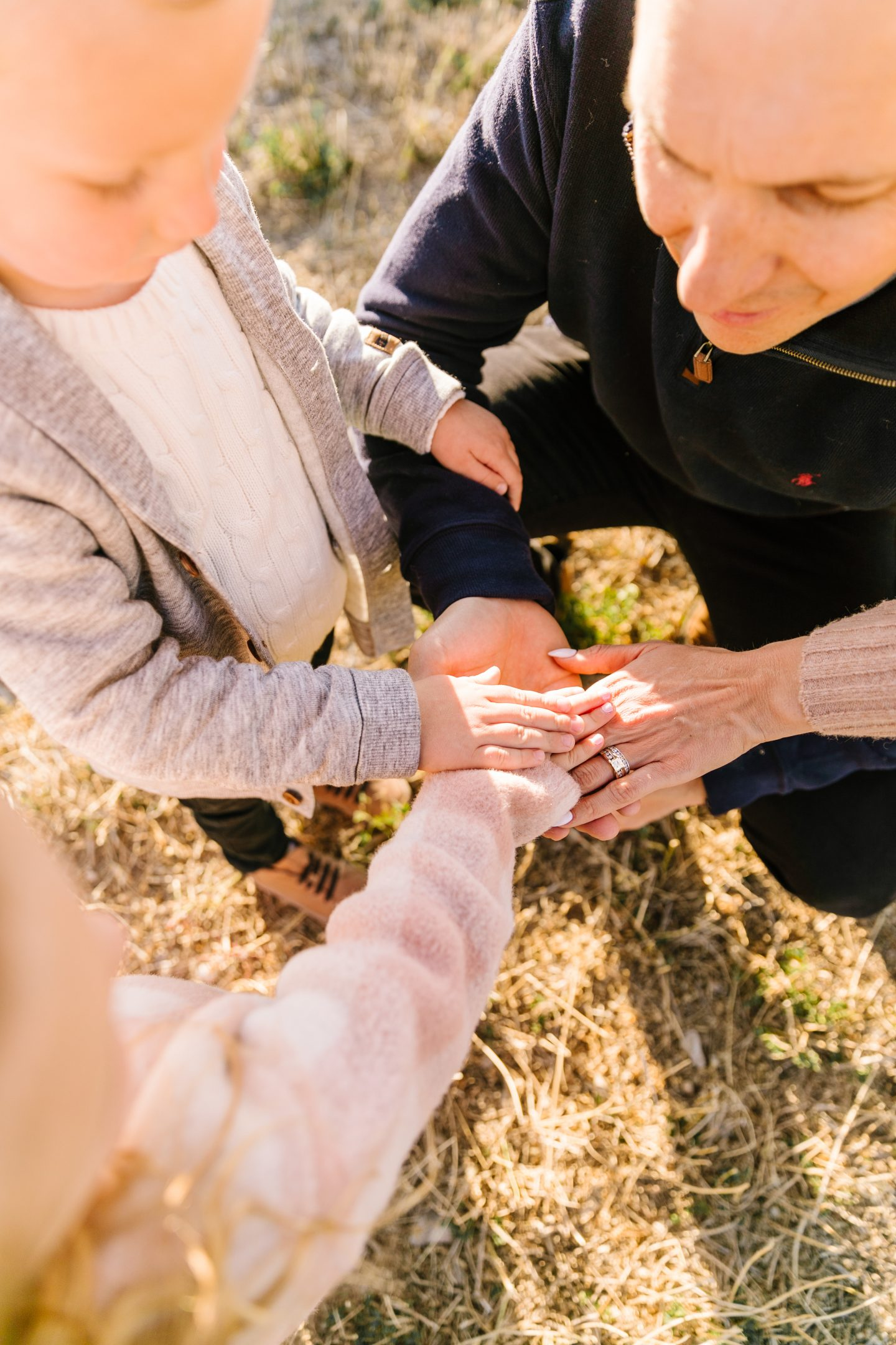 How to be More Present by popular San Diego lifestyle blog, Navy Grace: image of a dad touching hands with his two children.