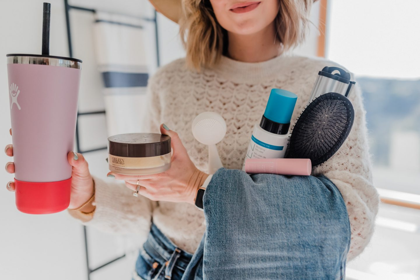 best 2019 purchases featured by top San Diego life and style blog, Navy Grace. | 2019 Favorite Products by popular San Diego life and style blog, Navy Grace: image of a woman standing in her bathroom and holding a drink tumbler, colleen rothschild facial product, hair brush, jeans, and St. Tropez self tanner.
