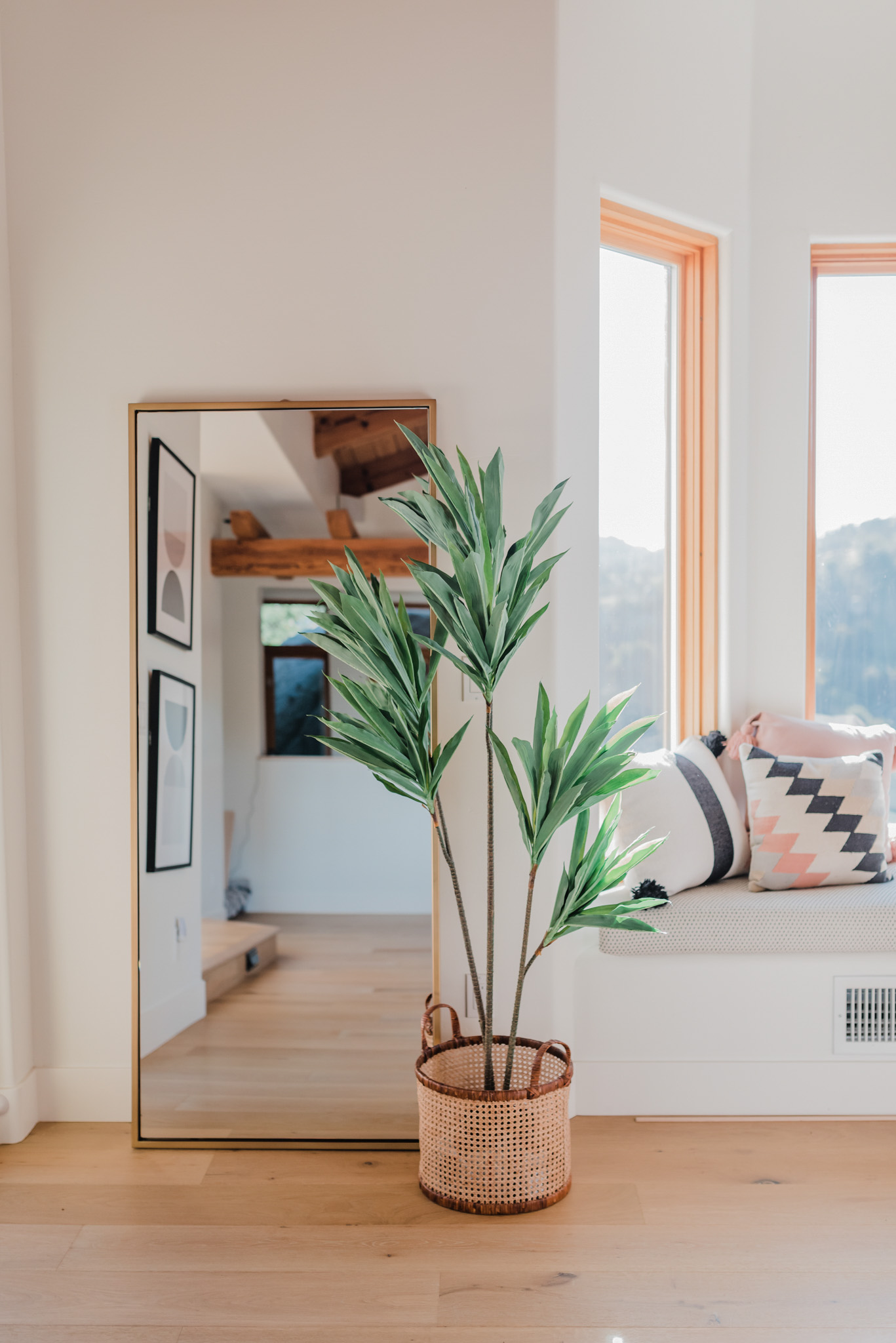 Best Full Length Mirrors by popular San Diego lifestyle blog, Navy Grace: image of a living room with natural light wood floors, a faux floor plant in a wicker basket, and a full length mirror.