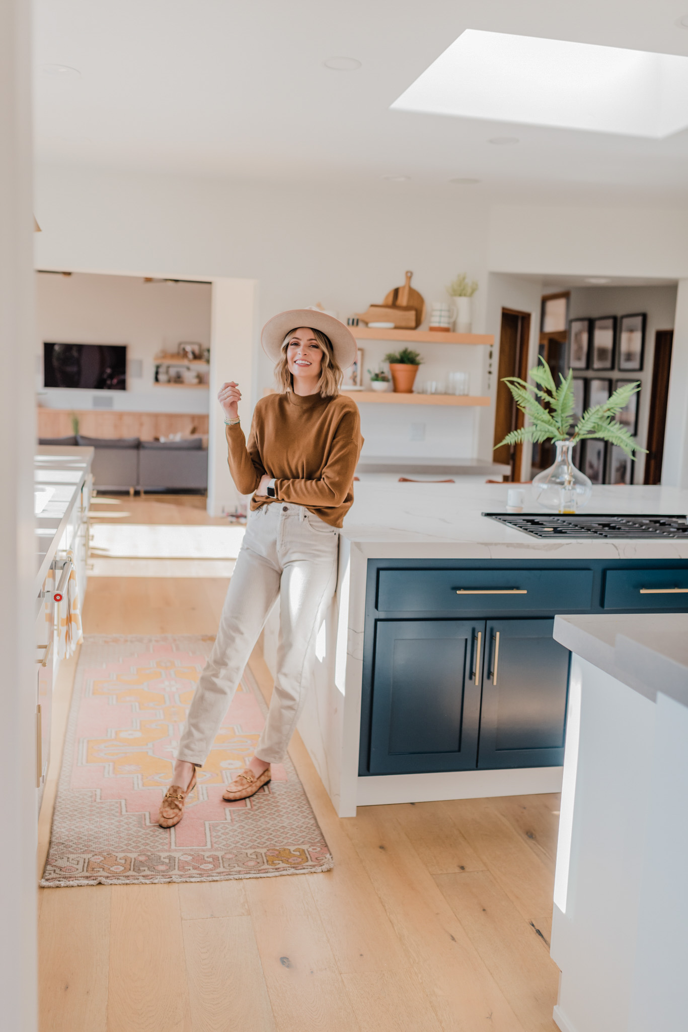 Spring Kitchen Wishlist by popular San Diego life and style blog, Navy Grace: image of a woman leaning against her kitchen island.