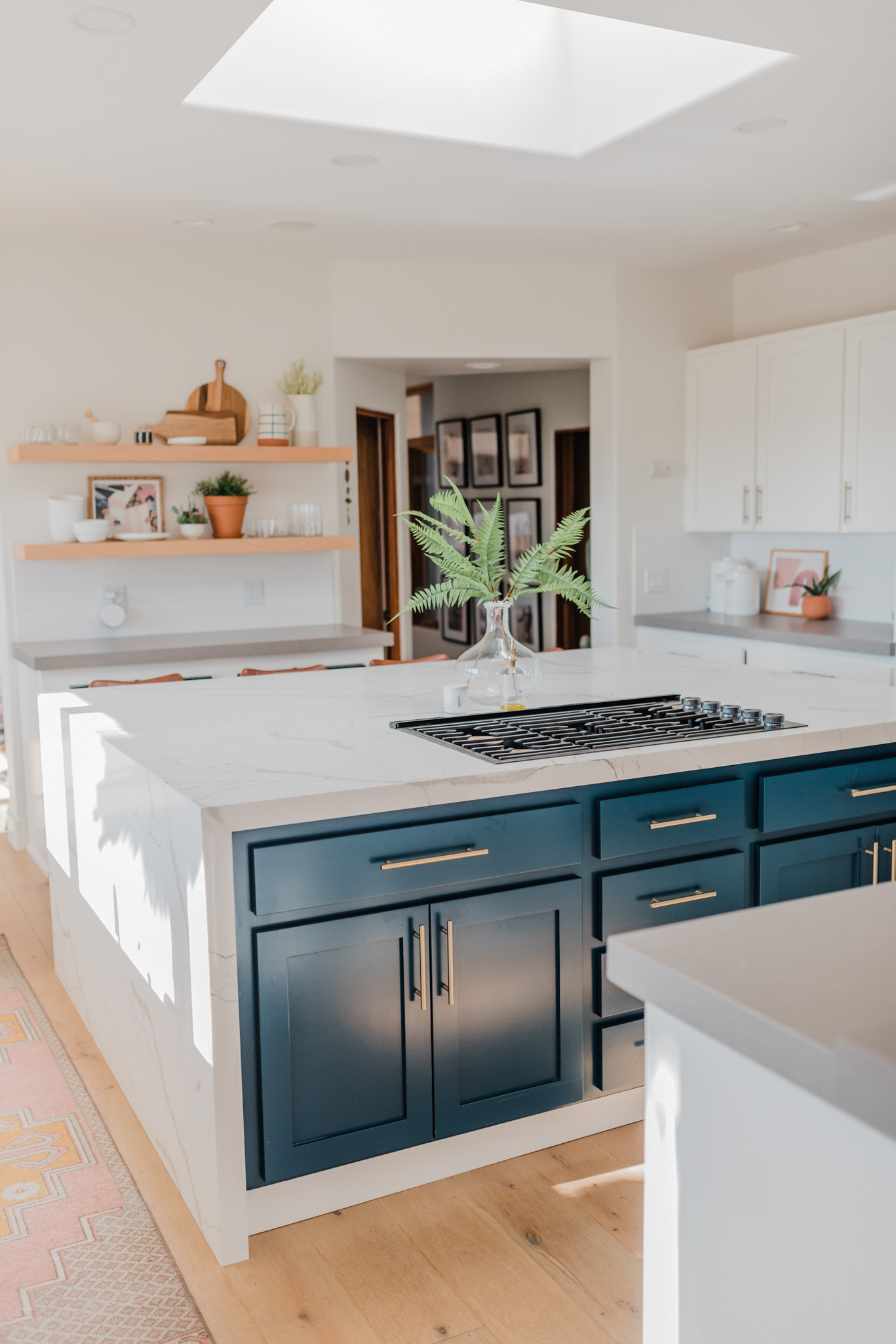 Spring Kitchen Wishlist by popular San Diego life and style blog, Navy Grace: image of a modern kitchen island with marble counter tops, blue drawers and cupboards, and a gas range.