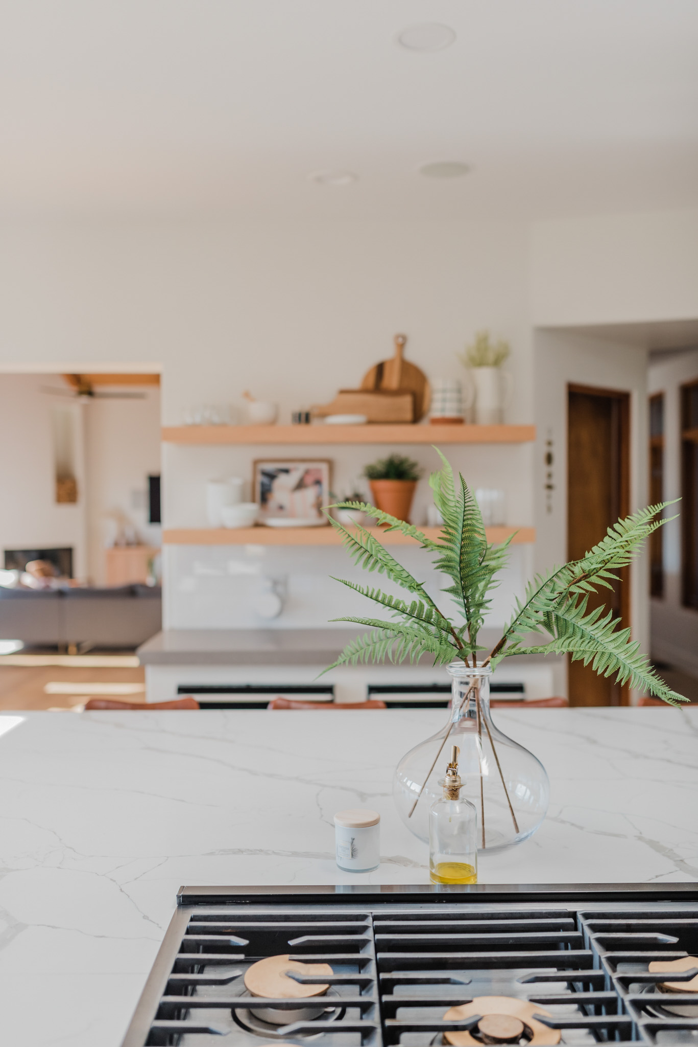 Spring Kitchen Wishlist by popular San Diego life and style blog, Navy Grace: image of a modern kitchen with marble counter tops, gas cooking range, floating wood shelves, leather barstools, and a clear glass vase with fern stems in it.