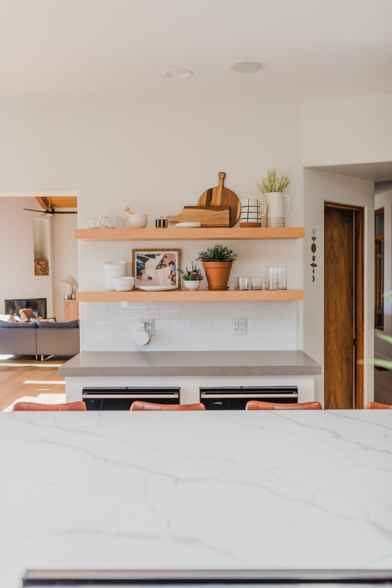 Spring Kitchen Wishlist by popular San Diego life and style blog, Navy Grace: image of a modern kitchen with marble counter tops, gas cooking range, floating wood shelves, and leather bar stools.