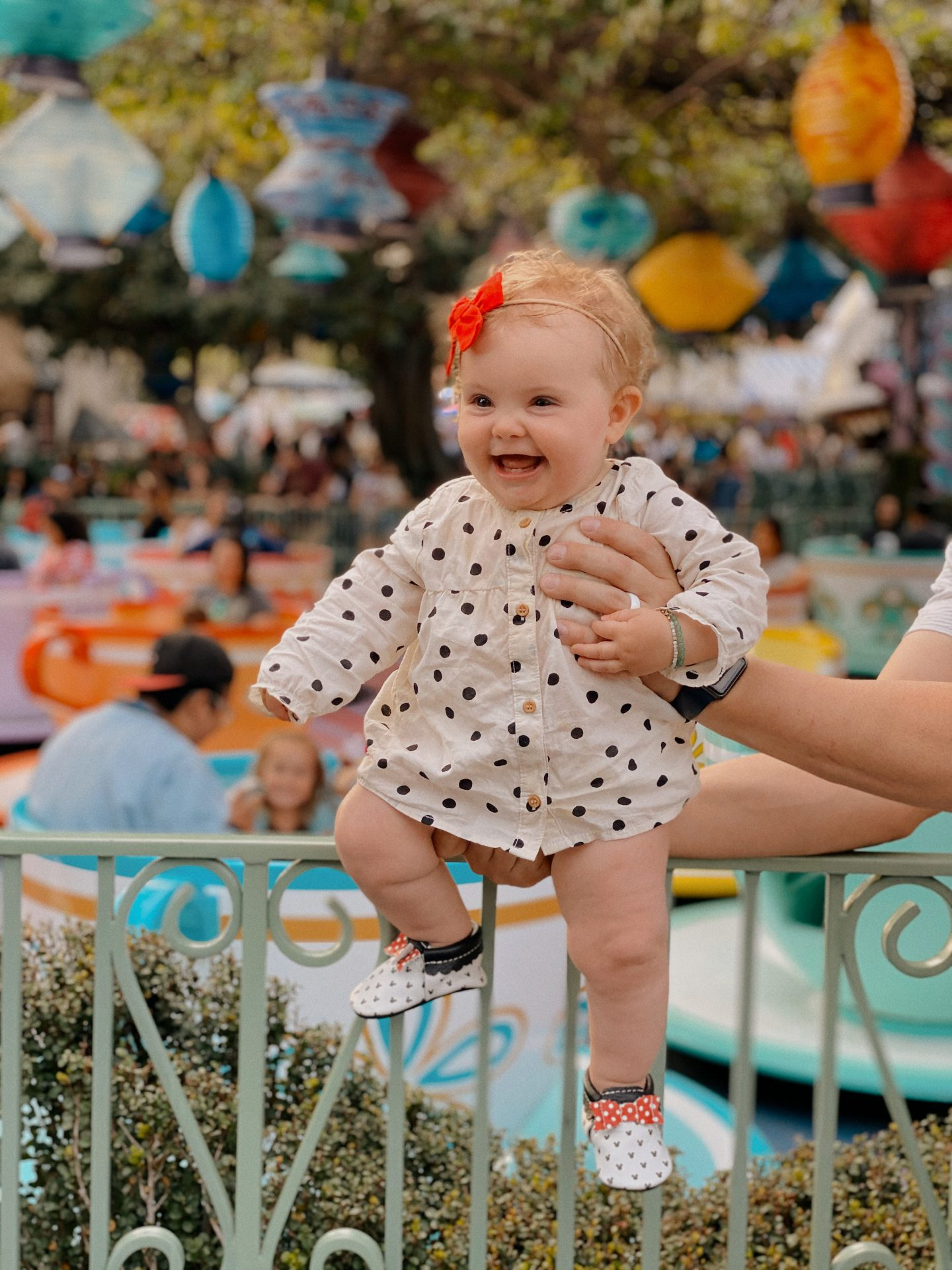 TOP 10 BEST DISNEYLAND TIPS FOR YOUR FAMILY featured by top San Diego blog, Navy Grace | Disneyland Tips by popular San Diego lifestyle blog, Navy Grace: image of a dad holding his baby girl in front of the tea cups ride at Disneyland.