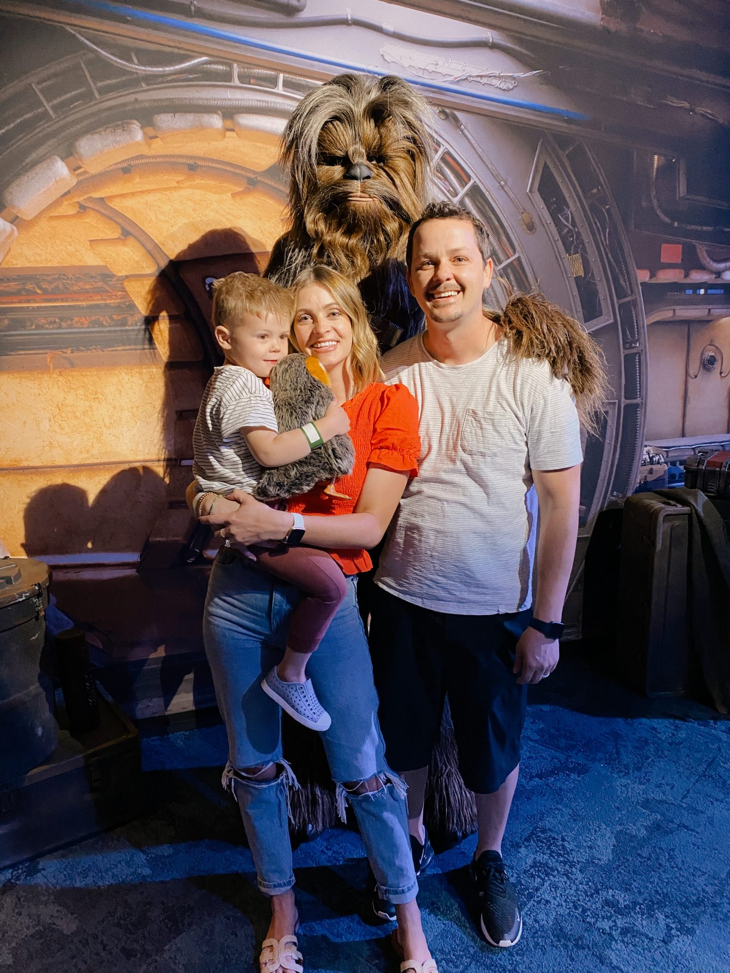 TOP 10 BEST DISNEYLAND TIPS FOR YOUR FAMILY featured by top San Diego blog, Navy Grace | Disneyland Tips by popular San Diego lifestyle blog, Navy Grace: image of mom, dad and their son standing with Chewbacca at Disneyland.