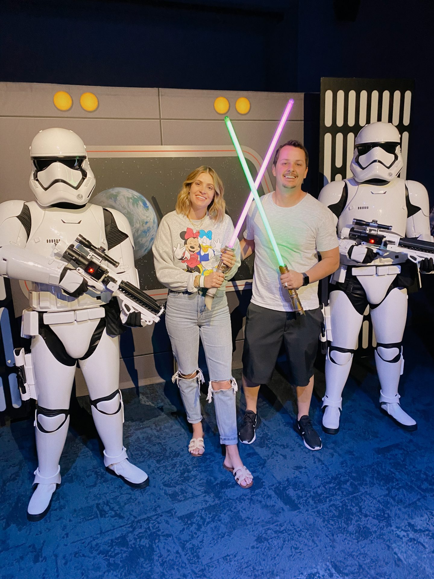 TOP 10 BEST DISNEYLAND TIPS FOR YOUR FAMILY featured by top San Diego blog, Navy Grace | Disneyland Tips by popular San Diego lifestyle blog, Navy Grace: image of a husband and wife holding light sabers and standing in between two storm troopers.