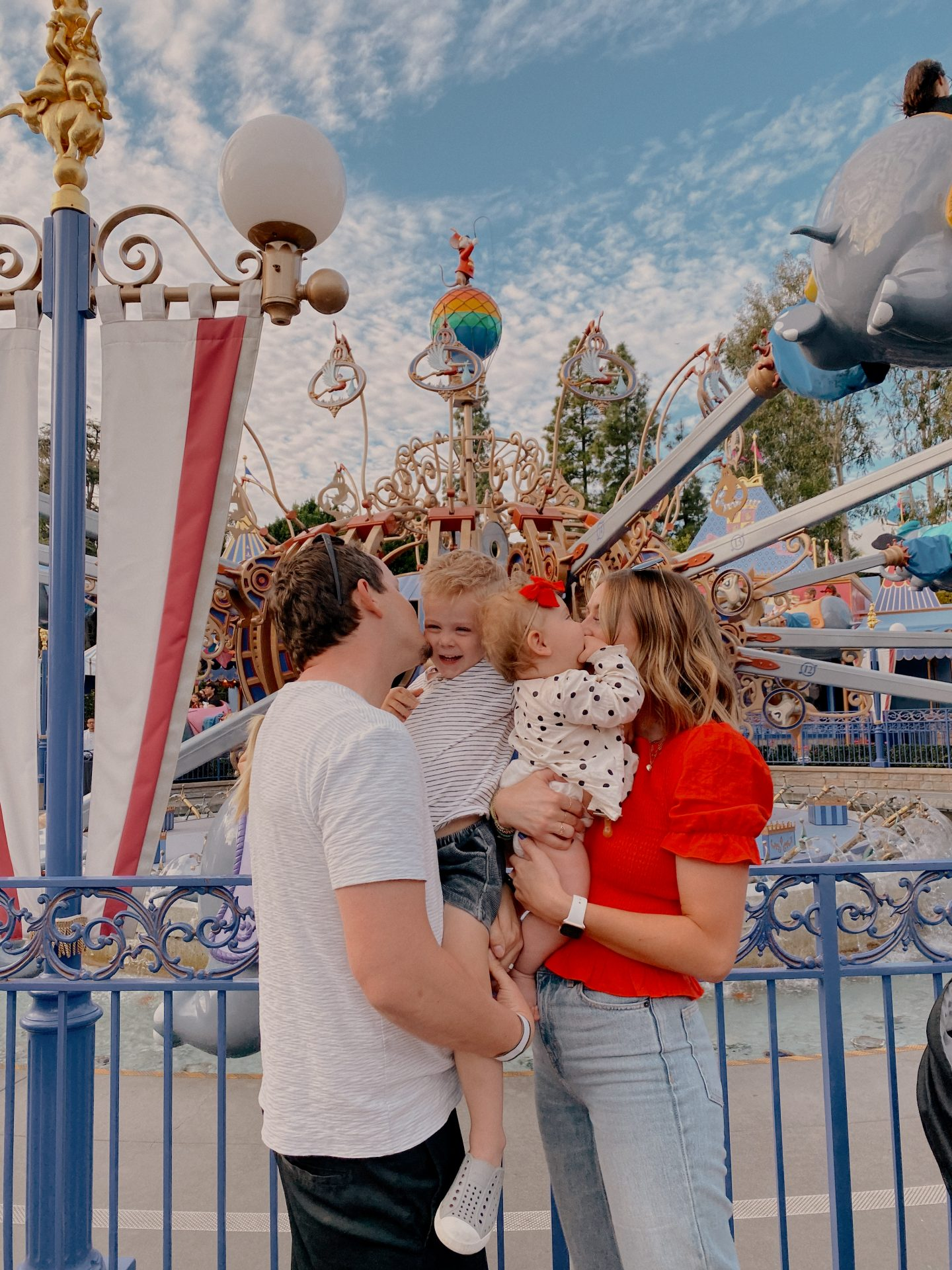 TOP 10 BEST DISNEYLAND TIPS FOR YOUR FAMILY featured by top San Diego blog, Navy Grace | Disneyland Tips by popular San Diego lifestyle blog, Navy Grace: image of a mom and dad kissing their two kids in front of the Dumbo ride at Disneyland.