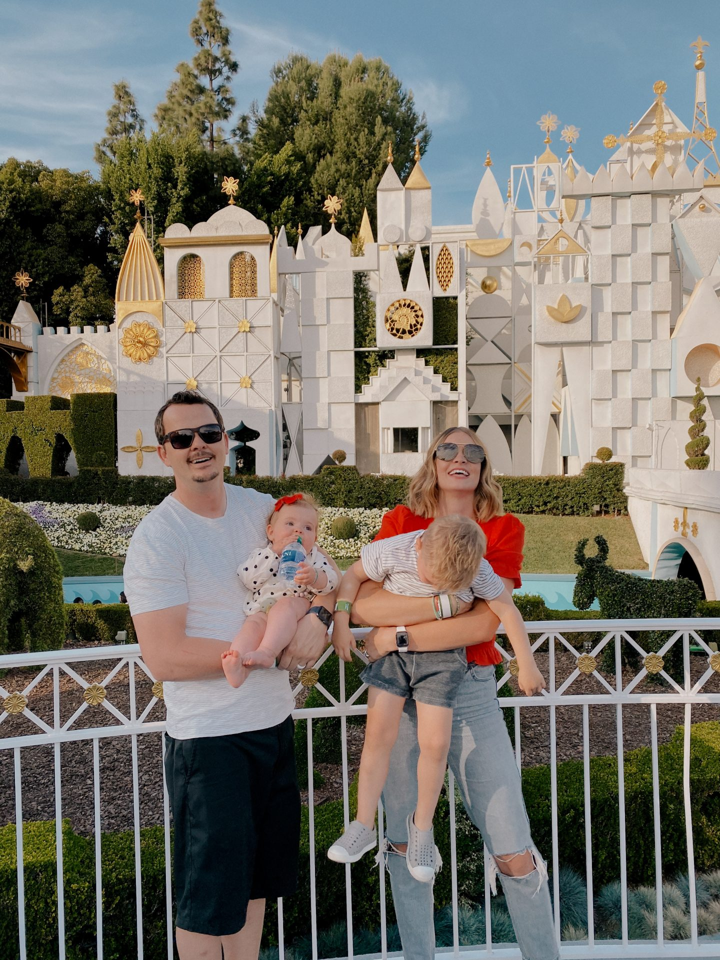 TOP 10 BEST DISNEYLAND TIPS FOR YOUR FAMILY featured by top San Diego blog, Navy Grace | Disneyland Tips by popular San Diego lifestyle blog, Navy Grace: image of a mom and dad holding their kids in front of the It's a Small World ride at Disneyland.