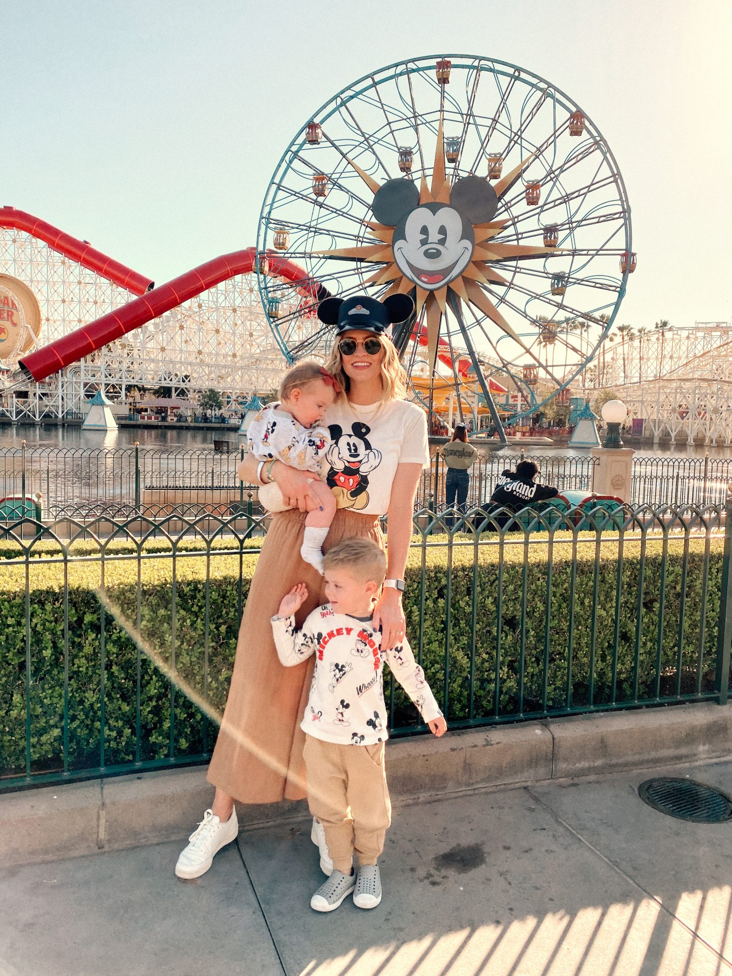 TOP 10 BEST DISNEYLAND TIPS FOR YOUR FAMILY featured by top San Diego blog, Navy Grace | Disneyland Tips by popular San Diego lifestyle blog, Navy Grace: image of a mom and her two kids standing in front of the ferris wheel at California Adventure theme park.