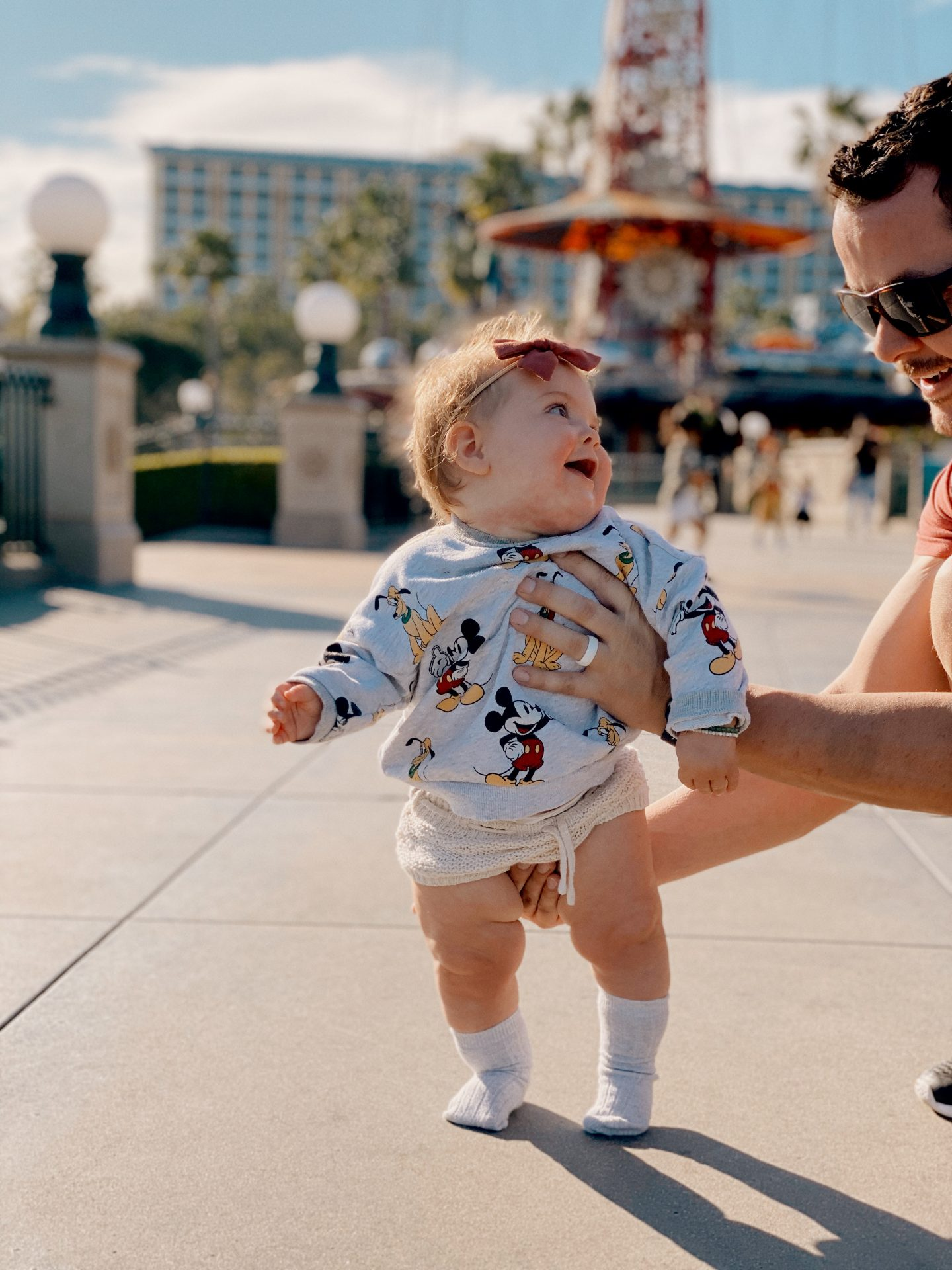 TOP 10 BEST DISNEYLAND TIPS FOR YOUR FAMILY featured by top San Diego blog, Navy Grace | Disneyland Tips by popular San Diego lifestyle blog, Navy Grace: image of a dad holding his baby girl who is wearing knit shorts and a grey Mickey Mouse t-shirt.