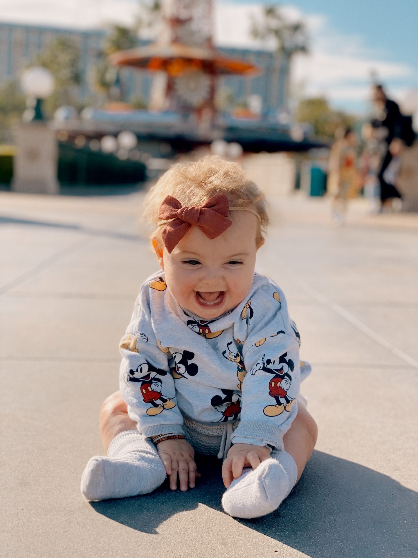 TOP 10 BEST DISNEYLAND TIPS FOR YOUR FAMILY featured by top San Diego blog, Navy Grace | Disneyland Tips by popular San Diego lifestyle blog, Navy Grace: image of a little girl sitting on the ground at Disneyland and wearing a Mickey Mouse shirt.