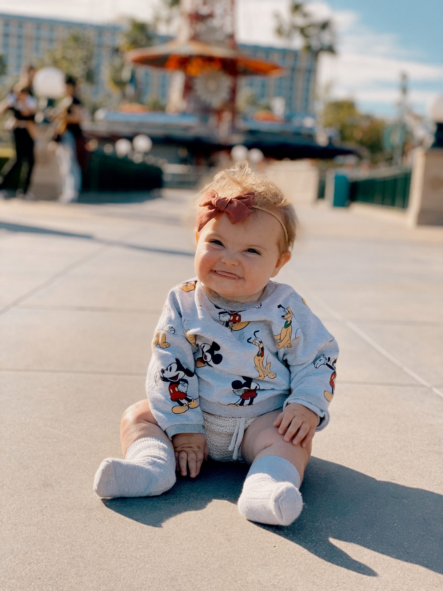 TOP 10 BEST DISNEYLAND TIPS FOR YOUR FAMILY featured by top San Diego blog, Navy Grace | Disneyland Tips by popular San Diego lifestyle blog, Navy Grace: image of a baby girl sitting on the ground at Disneyland and wearing a Mickey Mouse shirt.
