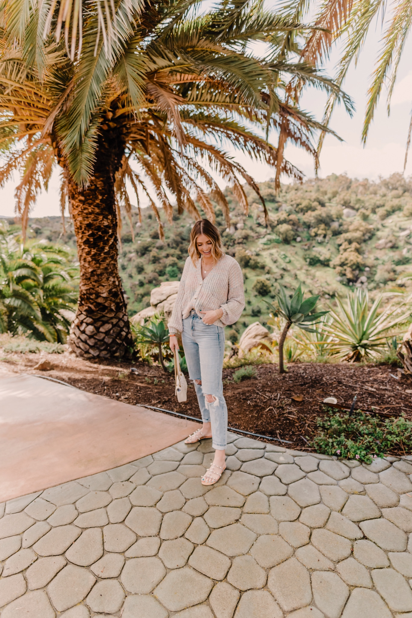 Spring arrivals featured by top San Diego fashion blog, Navy Grace. |2020 Spring Arrivals by popular San Diego fashion blog, Navy Grace: image of a woman sanding outside under a palm tree and wearing a Shopbop BB Dakota Double Rainbow Cardigan, TopShop Bleach Wash Double Rip Mom Tapered Jeans, Schutz Yarin Strappy Sandals, Nordstrom Gucci Small Matelassé Leather Shoulder Bag, and Gorjana Parker Wrap Necklace.