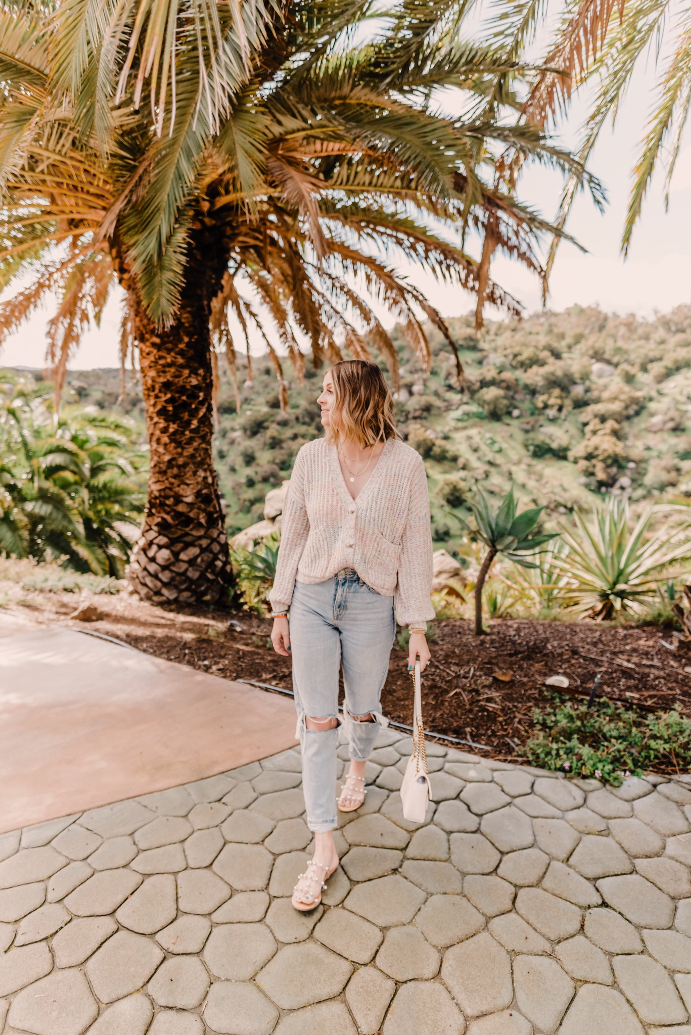 Spring arrivals featured by top San Diego fashion blog, Navy Grace. | 2020 Spring Arrivals by popular San Diego fashion blog, Navy Grace: image of a woman sanding outside under a palm tree and wearing a Shopbop BB Dakota Double Rainbow Cardigan, TopShop Bleach Wash Double Rip Mom Tapered Jeans, Schutz Yarin Strappy Sandals, Nordstrom Gucci Small Matelassé Leather Shoulder Bag, and Gorjana Parker Wrap Necklace.