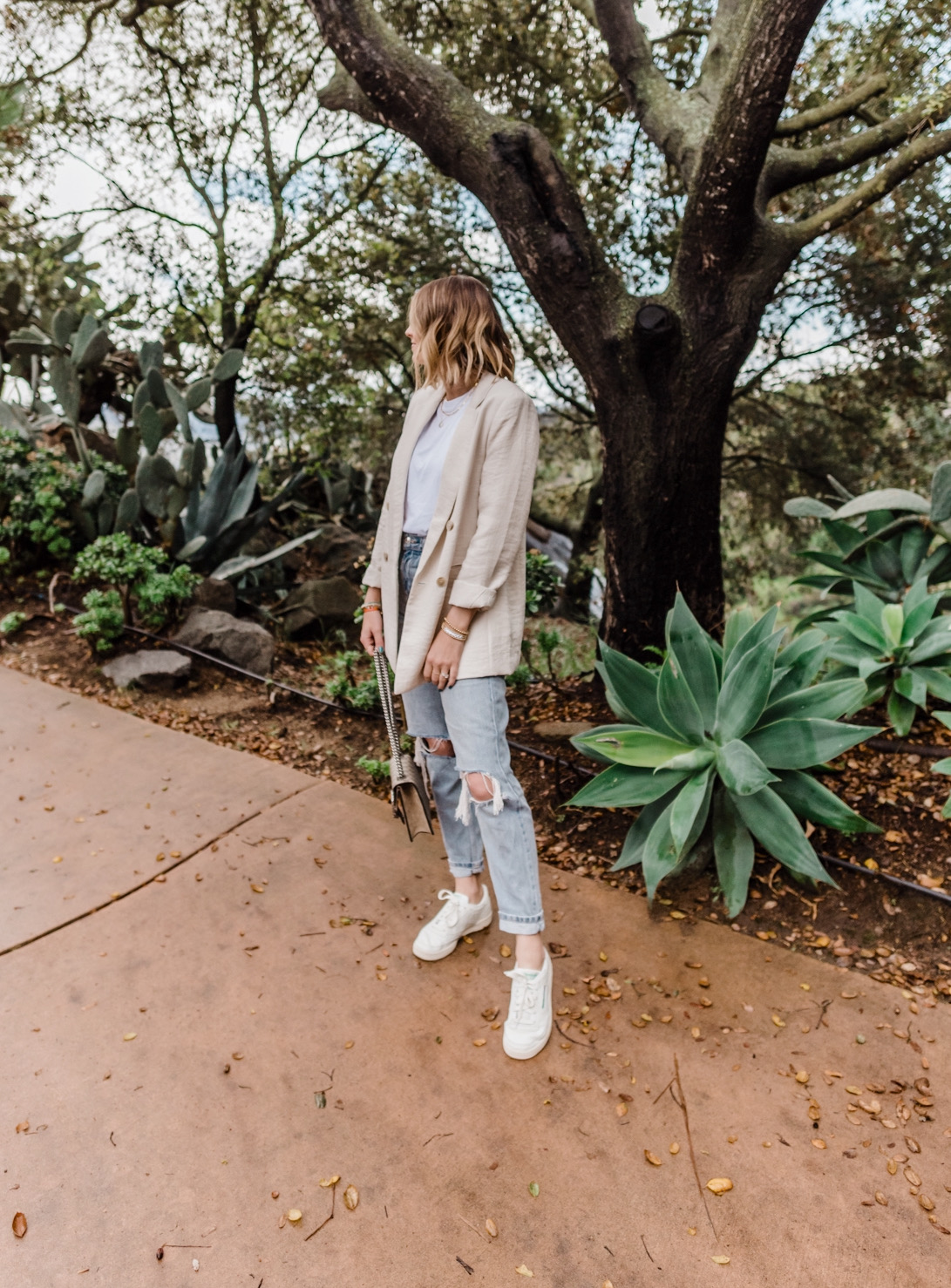 White Lifestyle Sneakers by popular San Diego fashion blog, Navy Grace: image of a woman wearing a H&M Linen-blend Blazer, TopShop Bleach Wash Double Rip Mom Tapered Jeans, Urban Outfitters Reebok Club C Vintage Sneaker, Nordstrom Small Matelassé Leather Shoulder Bag GUCCI, and Everlane The Easy Raglan Tee.