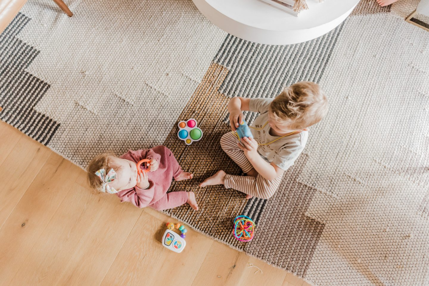 TODDLER EASTER BASKET GIFT IDEAS featured by top San Diego lifestyle blog, Navy Grace | Easter Basket Ideas for Toddlers by popular San Diego lifestyle blog, Navy Grace: image of a little boy sitting on the floor and playing with a camera next to his baby sister who is playing with some baby toys.