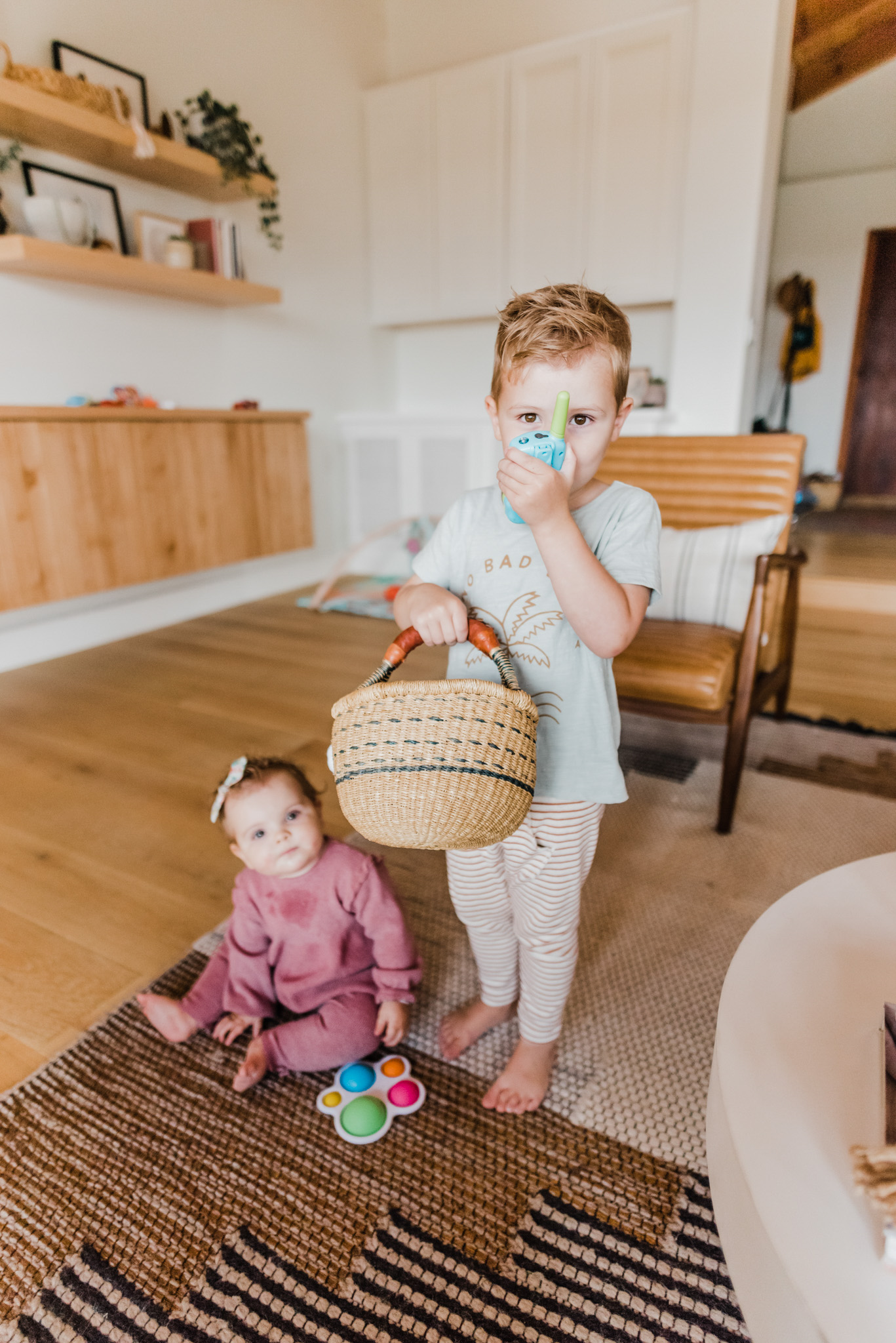 TODDLER EASTER BASKET GIFT IDEAS featured by top San Diego lifestyle blog, Navy Grace | Easter Basket Ideas for Toddlers by popular San Diego lifestyle blog, Navy Grace: image of a little boy holding a woven Easter basket in on hand a walkie talking in another.