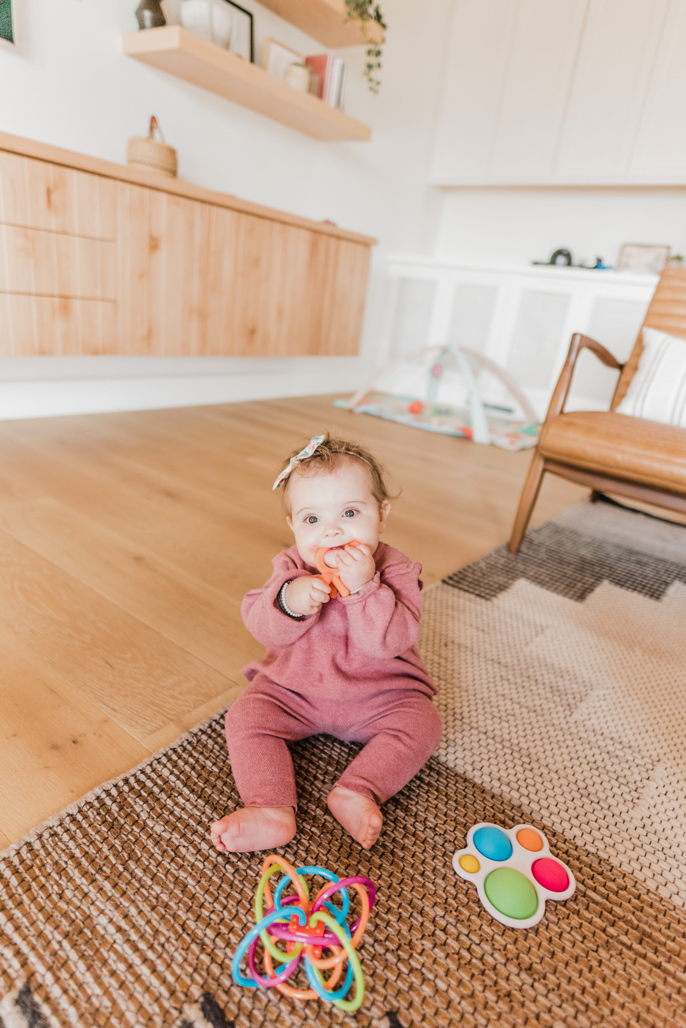 Easter Basket Gift Ideas by popular San Diego lifestyle blog, Navy Grace: image of a baby girl sitting on the floor and playing with baby toys.