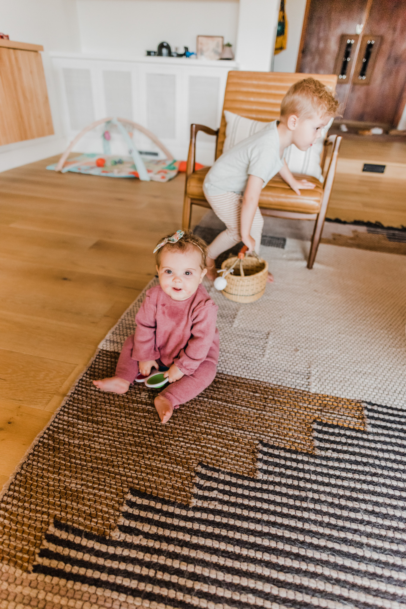 Easter Basket Gift Ideas by popular San Diego lifestyle blog, Navy Grace: image of a baby girl and young boy playing with toys on the floor.