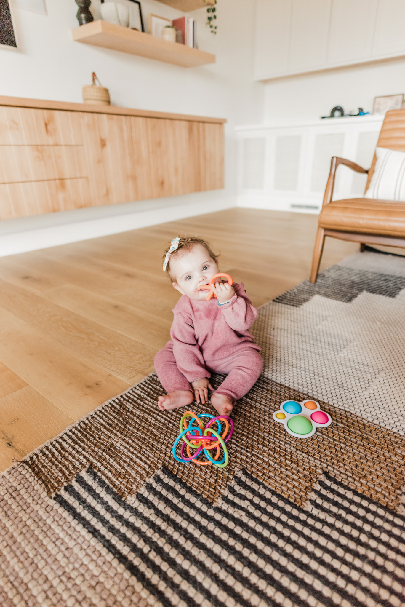 Easter Basket Gift Ideas by popular San Diego lifestyle blog, Navy Grace: image of a baby girl sitting on the floor and playing with some baby toys.