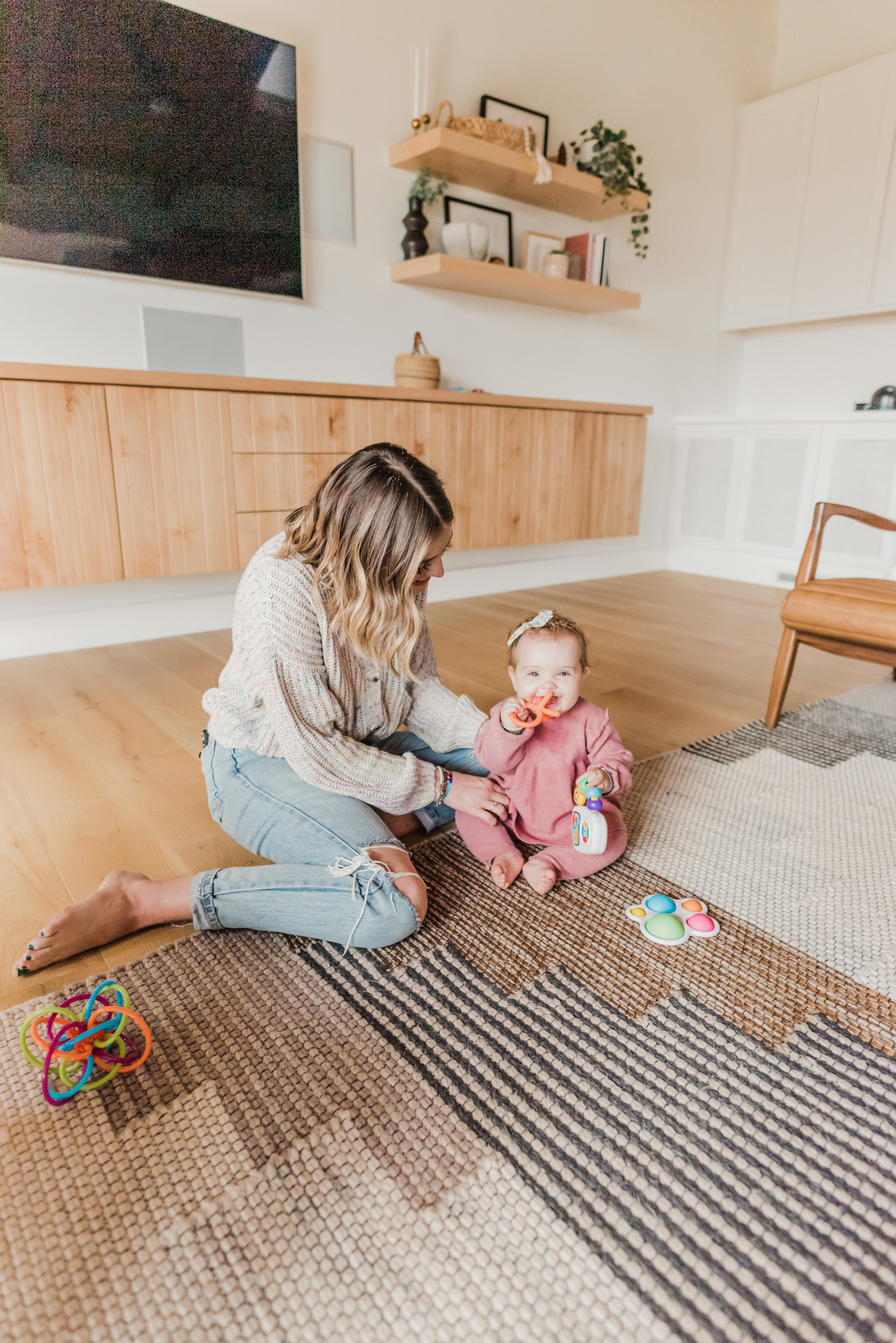 Easter Basket Gift Ideas by popular San Diego lifestyle blog, Navy Grace: image of a mom and baby girl sitting on floor and playing with baby toys together.