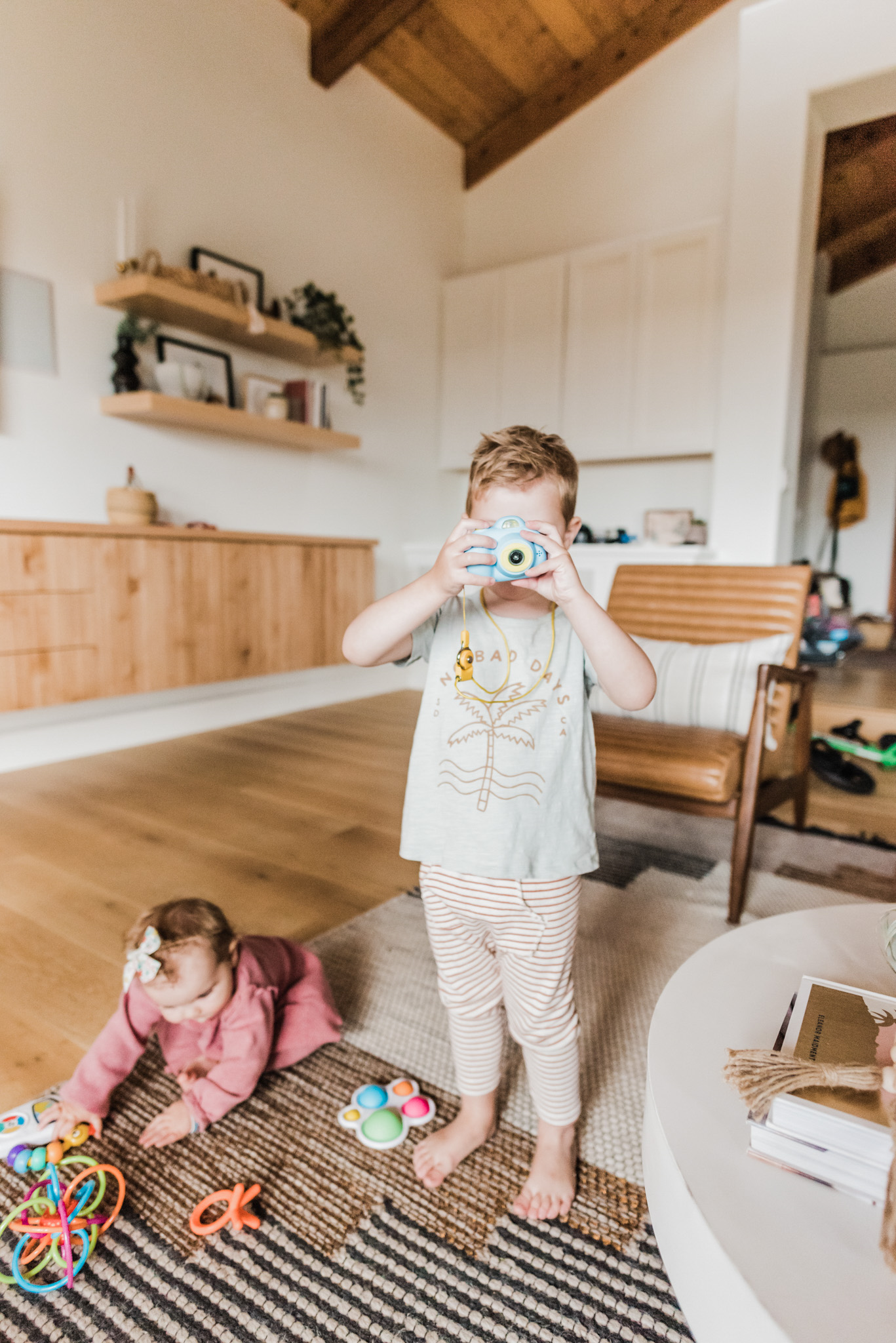 TODDLER EASTER BASKET GIFT IDEAS featured by top San Diego lifestyle blog, Navy Grace | Easter Basket Ideas for Toddlers by popular San Diego lifestyle blog, Navy Grace: image of a little boy holding a camera and a little girl playing with some toys on the floor.