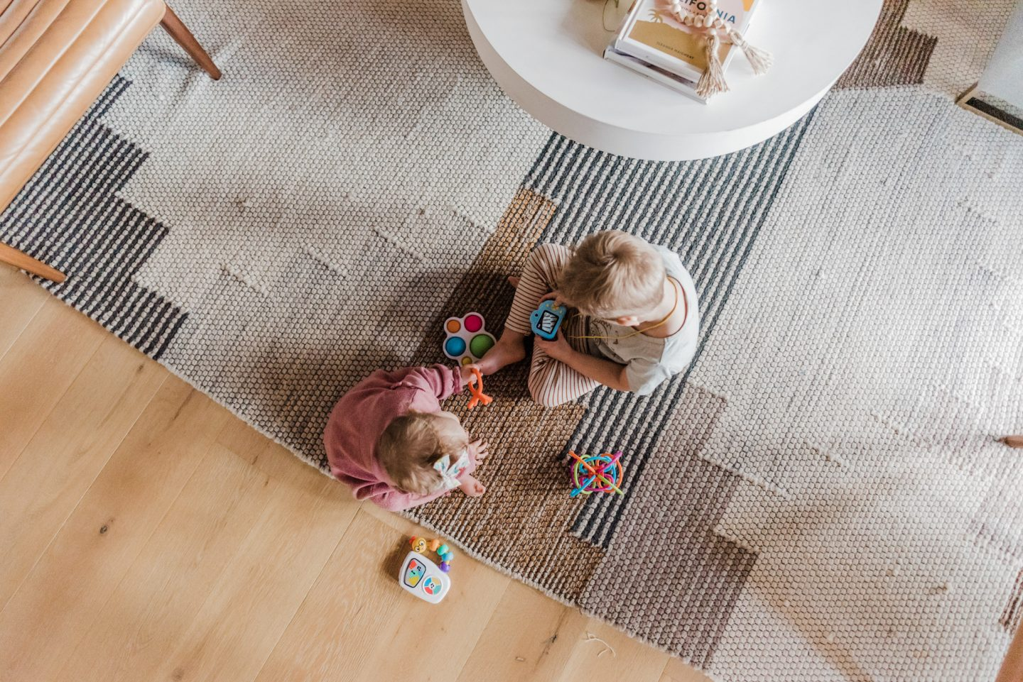 TODDLER EASTER BASKET GIFT IDEAS featured by top San Diego lifestyle blog, Navy Grace | Easter Basket Ideas for Toddlers by popular San Diego lifestyle blog, Navy Grace: image of a two kids sitting on the floor and playing with some toys.