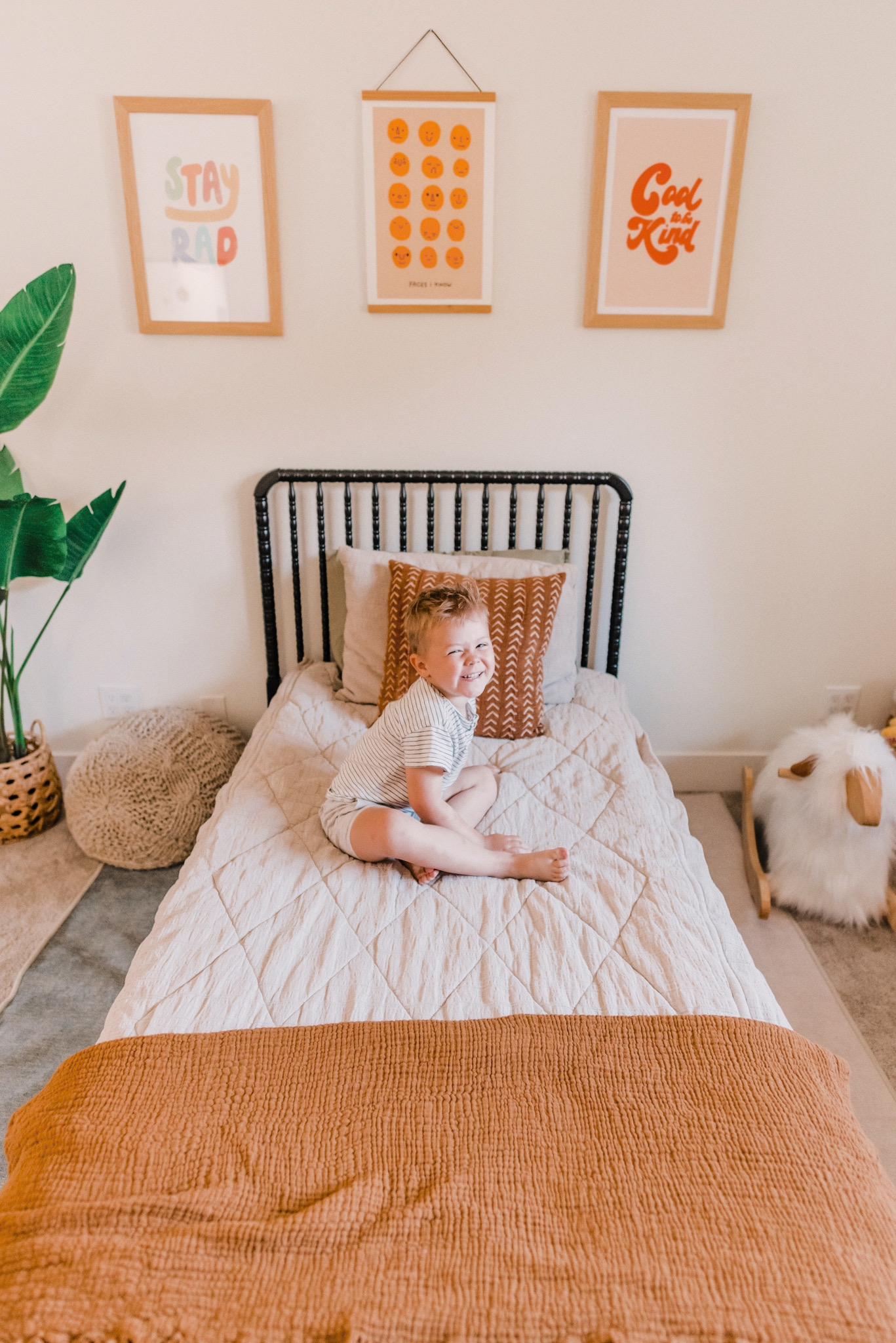Barn and Willow by popular San Diego life and style blog, Navy Grace: image of a little boy sitting on a bed in a bedroom decorated with Barn and Willow drapery, Wayfair Jenny Lind Twin Platform Bed, Ruggable Domo Sage Rug, Urban Outfitters Rhianna Marie Chan Cool To Be Kind Art Print, Urban Outfitters  Hover to zoom.  Hiller Goodspeed Faces I Know Art Print, Urban Outfitters Phirst Stay Rad Colors Art Print, H&M Cotton Throw, and Amazon One 5 foot Artificial Silk Bird of Paradise Palm Tree Potted Plant.