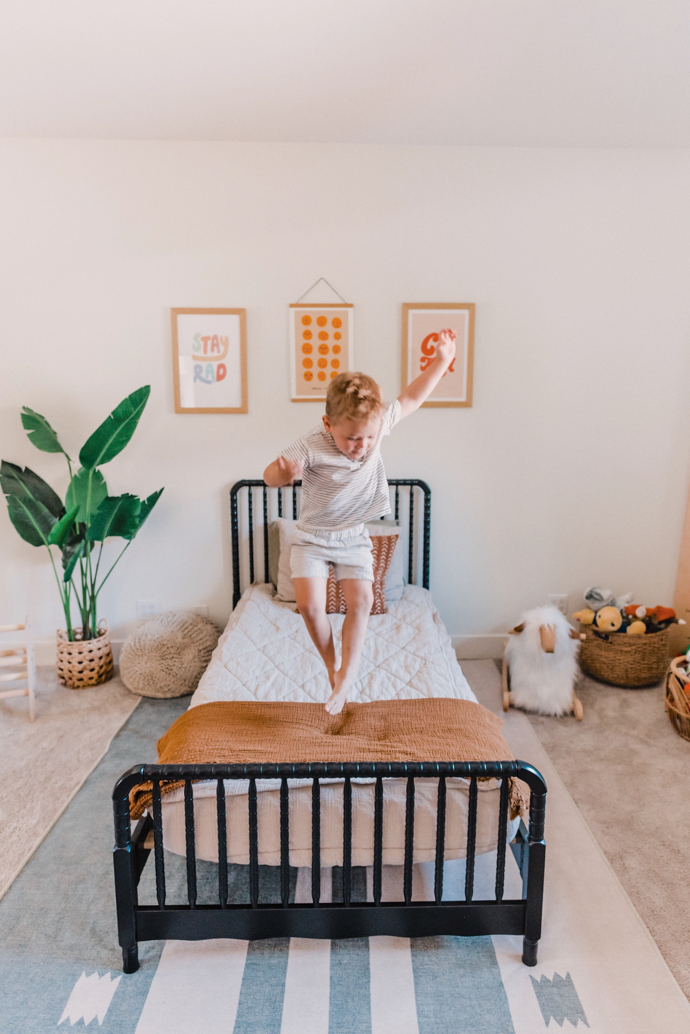 Barn and Willow by popular San Diego life and style blog, Navy Grace: image of a boy jumping on a bed in a bedroom decorated with Barn and Willow drapery, Wayfair Jenny Lind Twin Platform Bed, Ruggable Domo Sage Rug, Urban Outfitters Rhianna Marie Chan Cool To Be Kind Art Print, Urban Outfitters  Hover to zoom.  Hiller Goodspeed Faces I Know Art Print, Urban Outfitters Phirst Stay Rad Colors Art Print, H&M Cotton Throw, and Amazon One 5 foot Artificial Silk Bird of Paradise Palm Tree Potted Plant.