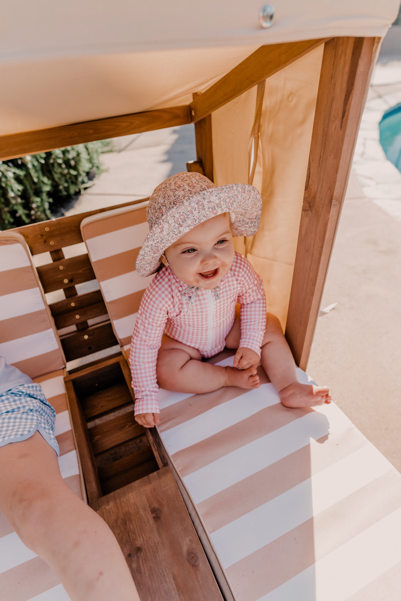 Kids Swimsuits by popular San Diego fashion blog, Navy Grace: image of two kids sitting together child size cabana and wearing blue and light pink gingham swimsuits and rash guards.