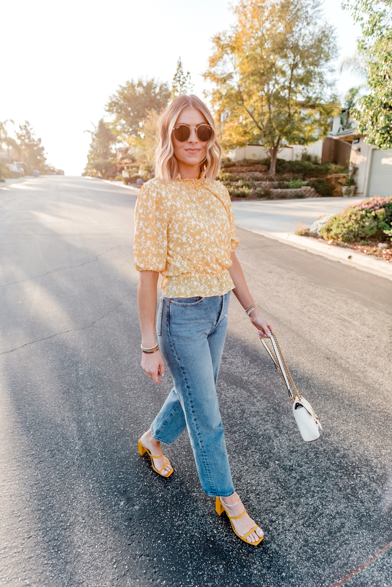 Items Bought in March by popular San Diego life and style blog, Navy Grace: image of a woman standing in a road and wearing a ShopBop BB Dakota Printed Bubble Top, ShopBop Levi's Ribcage Straight Ankle Jeans, Nordstrom 51mm Aviator Sunglasses RAY-BAN, yellow sandal slide heels and Nordstrom Small Matelassé Leather Shoulder Bag GUCCI.