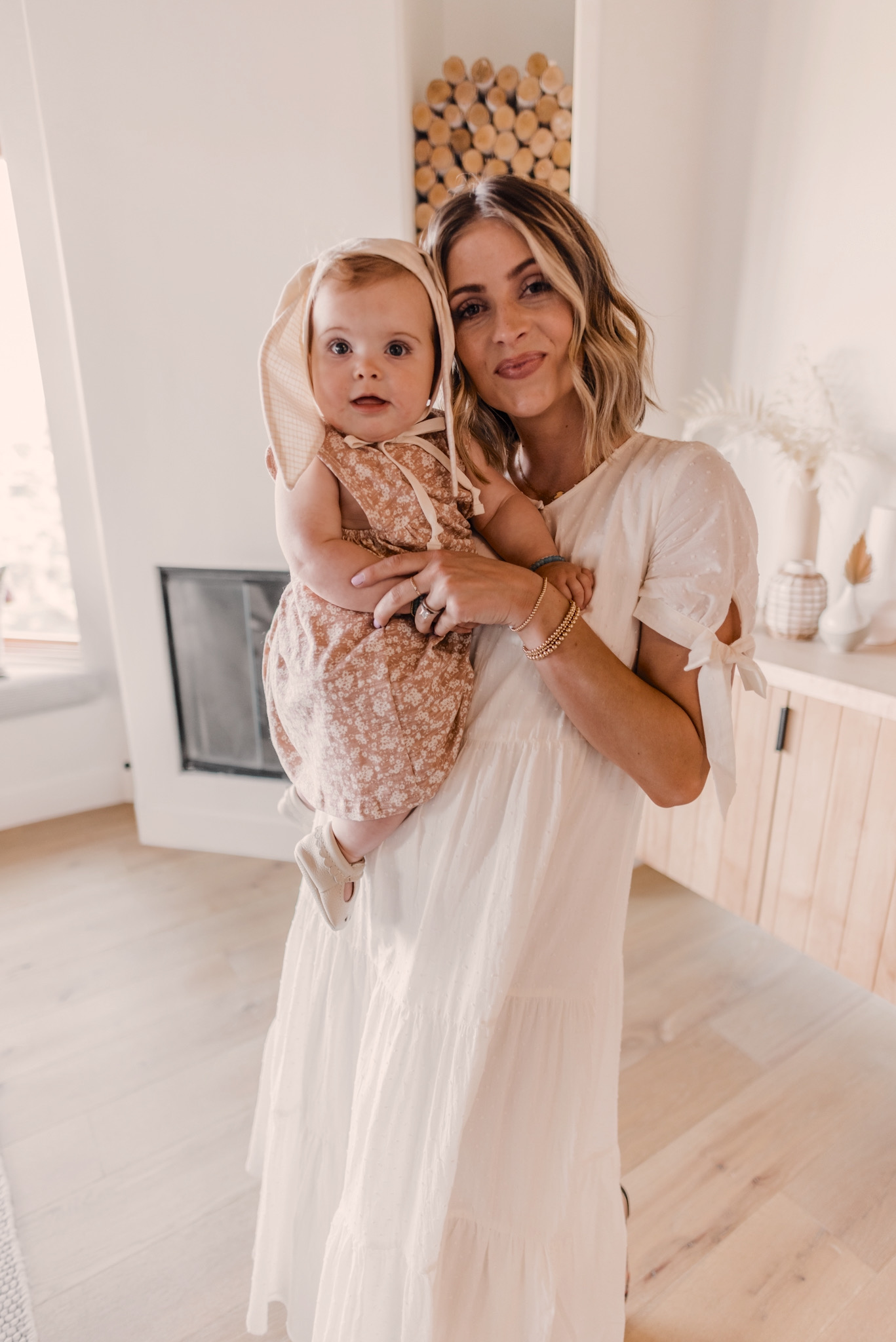 TOP 10 CUTE SPRING WHITE DRESSES featured by top San Francisco fashion blog, Navy Grace: image of a blonde woman wearing a Madewell maxi dress. | White Spring Dresses by popular San Diego fashion blog, Navy Grace: image of a woman holding her baby girl and wearing a Madewell Tie-Sleeve Tiered Midi Dress in Swiss Dot, Shashi Tilu Set of 2 Bracelets, Loeffler Randall Daphne Knot Flat Sandals, and holding a Gigi New York TORI TOTE White Pebble Grain.