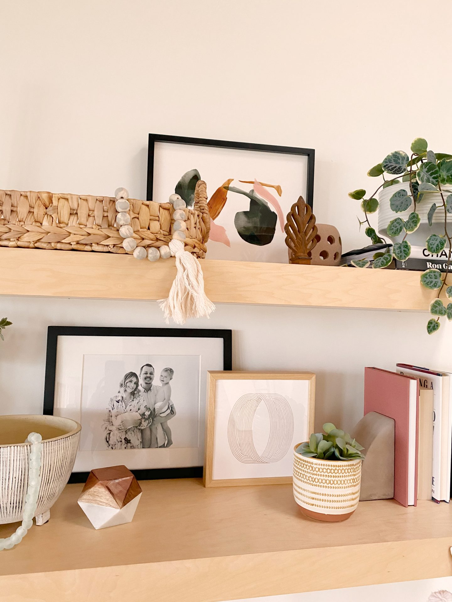 Minted Art by popular life and style blog, Navy Grace: image of a framed Minted Calm Forest print and Minted Thumbprint art work on wooden shelves with woven baskets, wooden and marble knick knacks, books, and house plants.