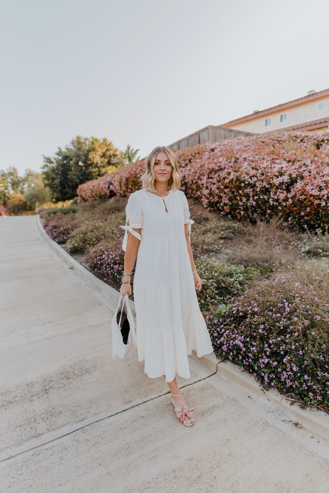 TOP 10 CUTE SPRING WHITE DRESSES featured by top San Francisco fashion blog, Navy Grace: image of a blonde woman wearing a Madewell maxi dress. | White Spring Dresses by popular San Diego fashion blog, Navy Grace: image of a woman walking outside and wearing a Madewell Tie-Sleeve Tiered Midi Dress in Swiss Dot, Shashi Tilu Set of 2 Bracelets, Loeffler Randall Daphne Knot Flat Sandals, and holding a Gigi New York TORI TOTE White Pebble Grain.