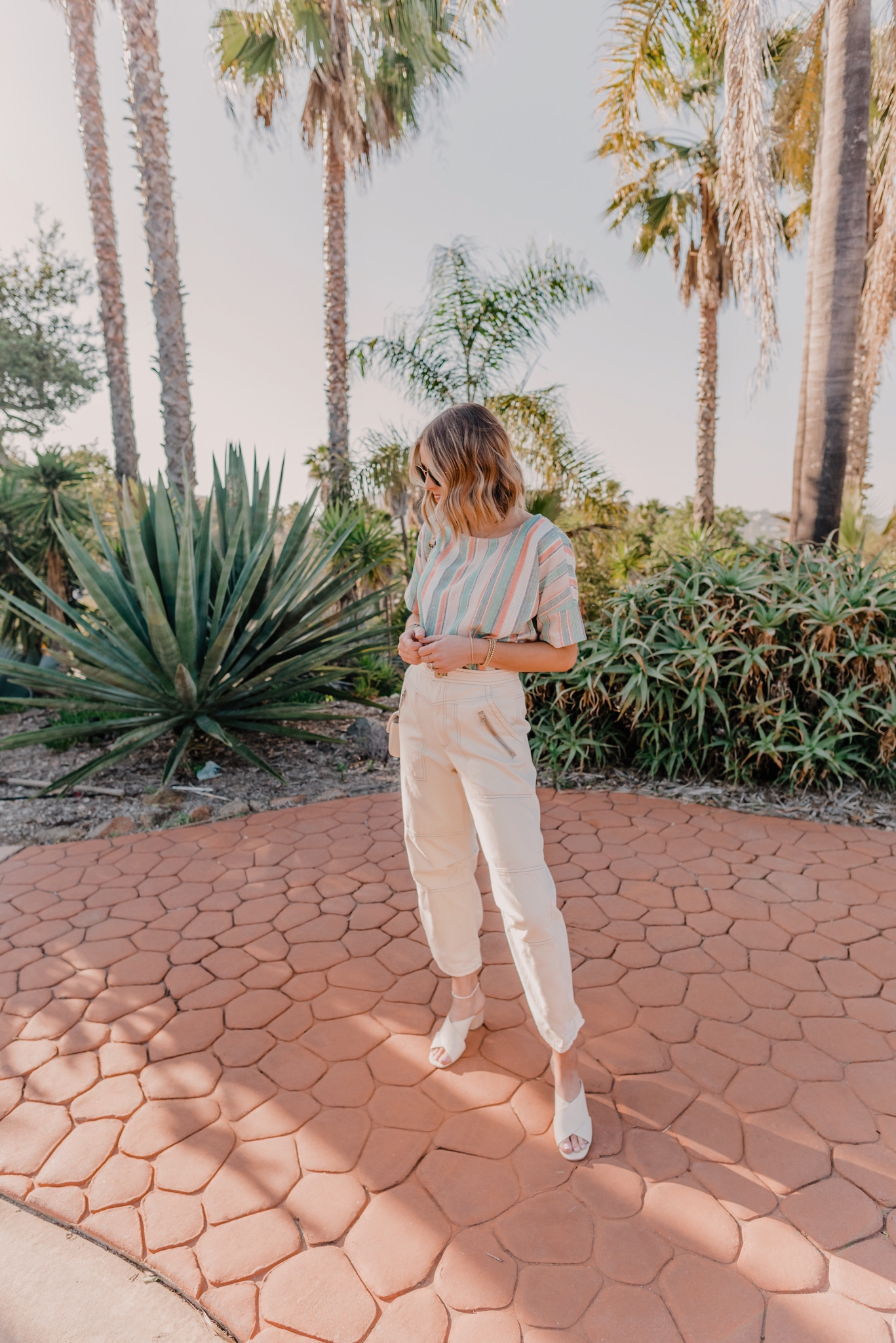 Daily Quarantine Schedule by popular San Diego lifestyle blog, Navy Grace: image of a woman standing outside by some palm trees and wearing a THE ODELLS: EASY PULL OVER TOP, Free People Free People Misty Road Pants, Shashi Tilu Set of 2 Bracelets, and Nordstrom 51mm Aviator Sunglasses RAY-BAN.