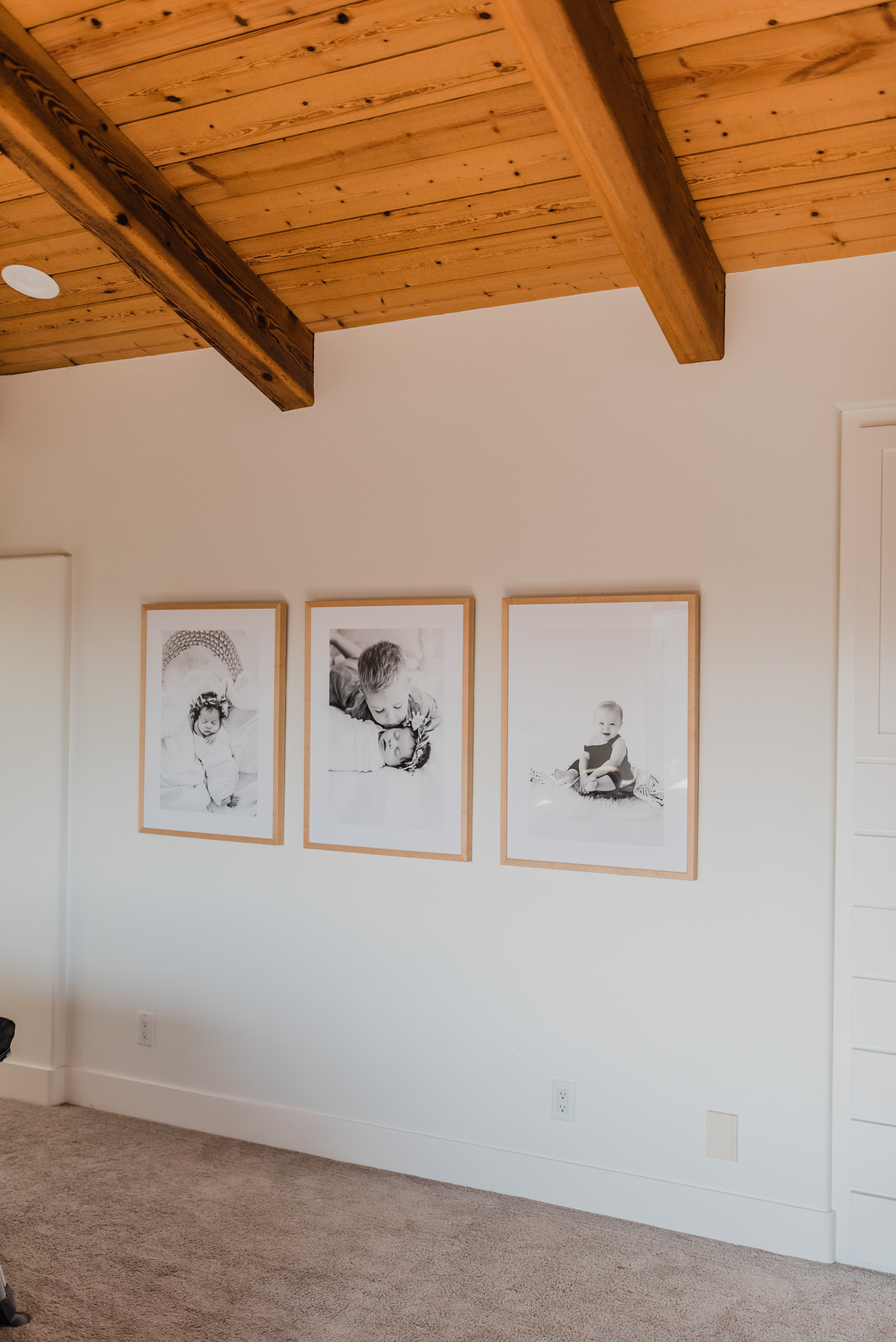 Frambridge Frames by popular San Diego life and style blog, Navy Grace: image of a wall in a home with multiple natural wood Framebridge frames hanging on it.