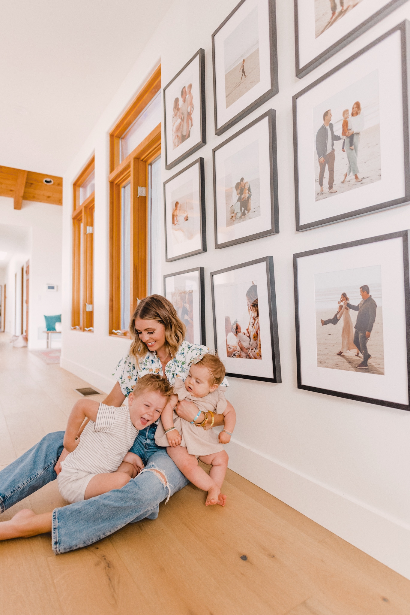 Frambridge Frames by popular San Diego life and style blog, Navy Grace: image of a mom and her two kids sitting int the hallway of their home next to a wall will a lot of Framebridge frames hung on it.