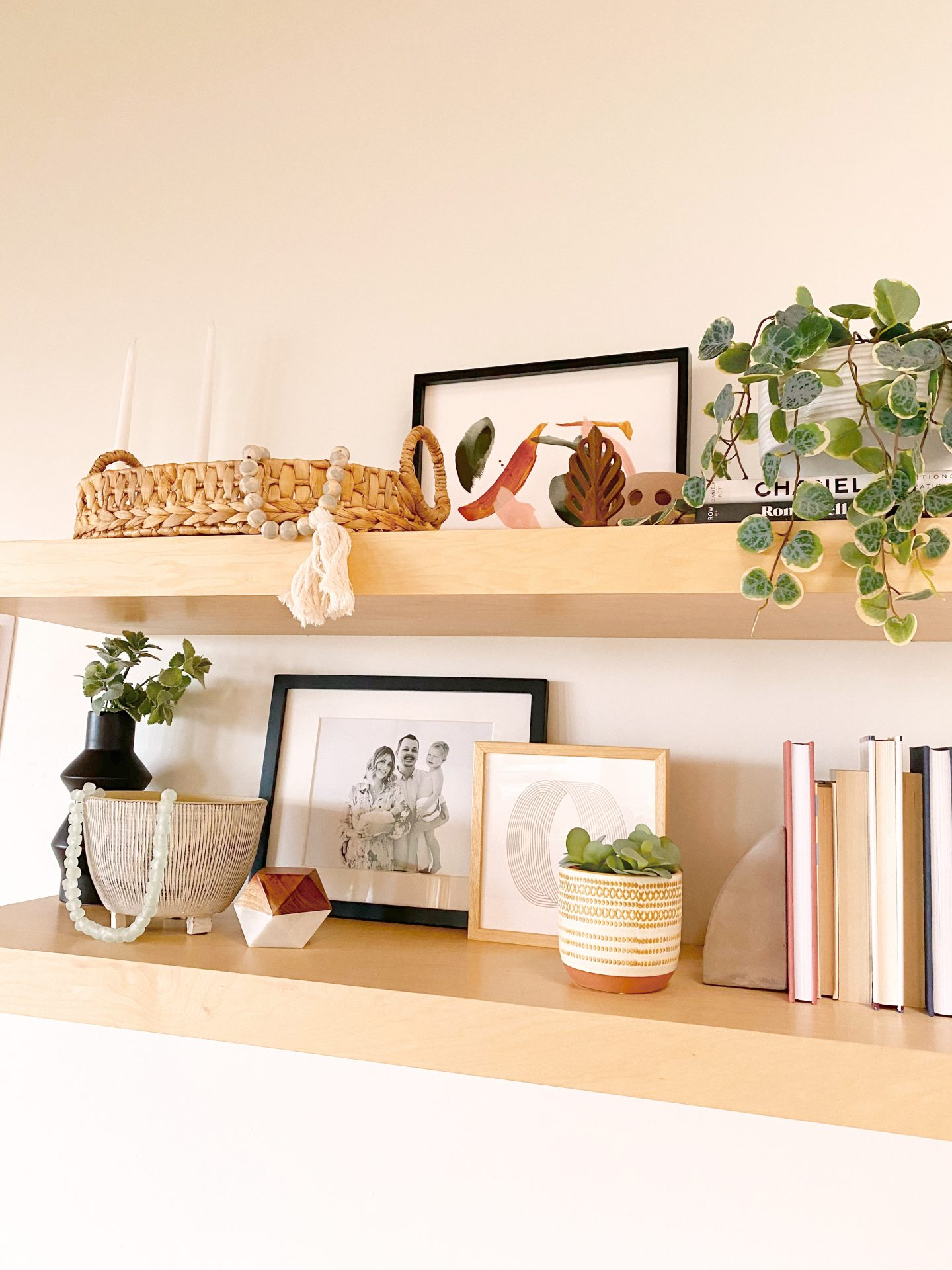 Frambridge Frames by popular San Diego life and style blog, Navy Grace: image of two floating shelves with framebridge frames, a potted plant, books, and a straw basket on it.