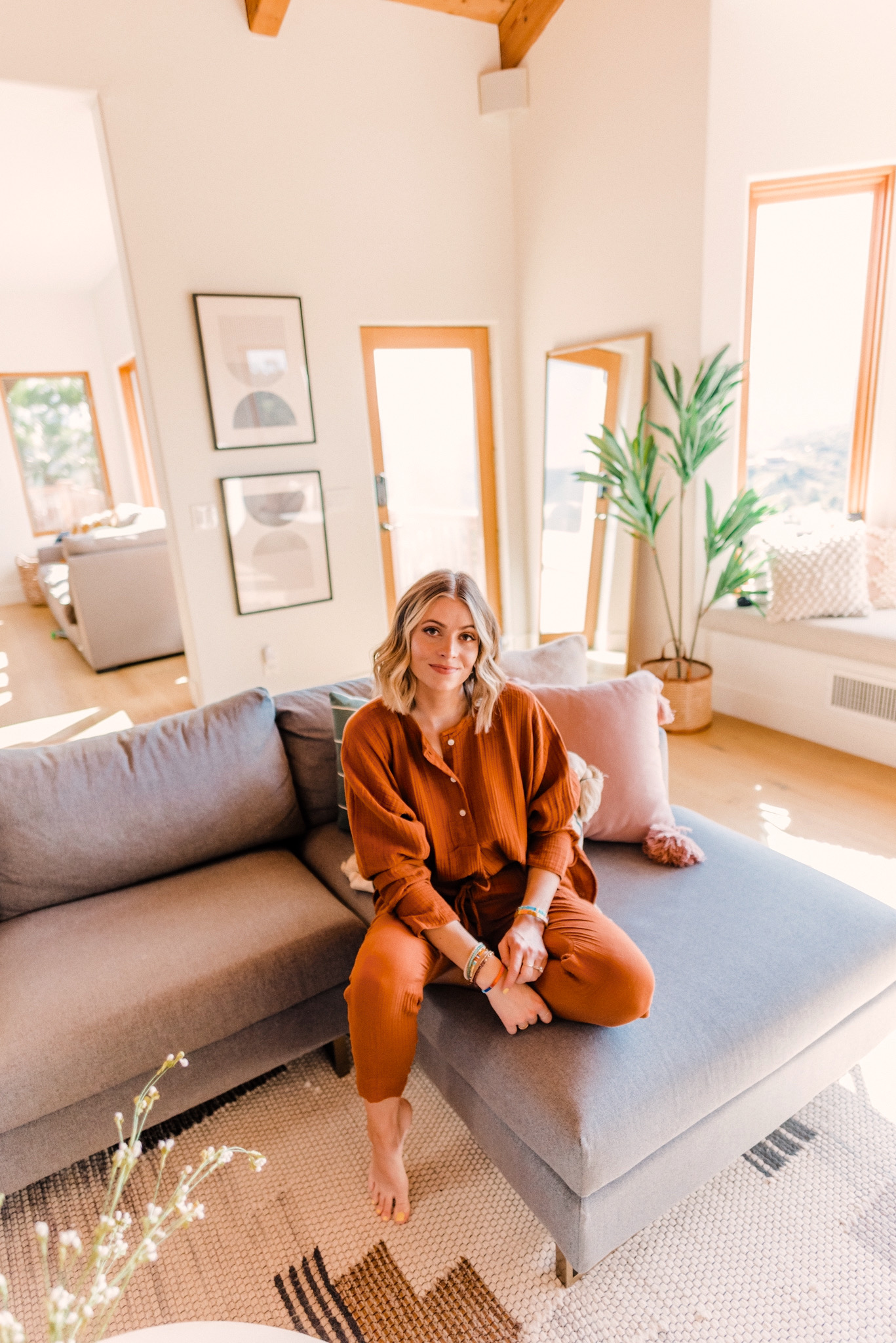 Favorite Things on Amazon by popular San Diego life and style blog, Navy Grace: image of a woman sitting on a grey sectional couch in her living room and wearing a Lou & Grey Triple Cloth Henley Tunic Shirt, Lou & Grey Triple Cloth Joggers, and Gorjana Parker Wrap Necklace.