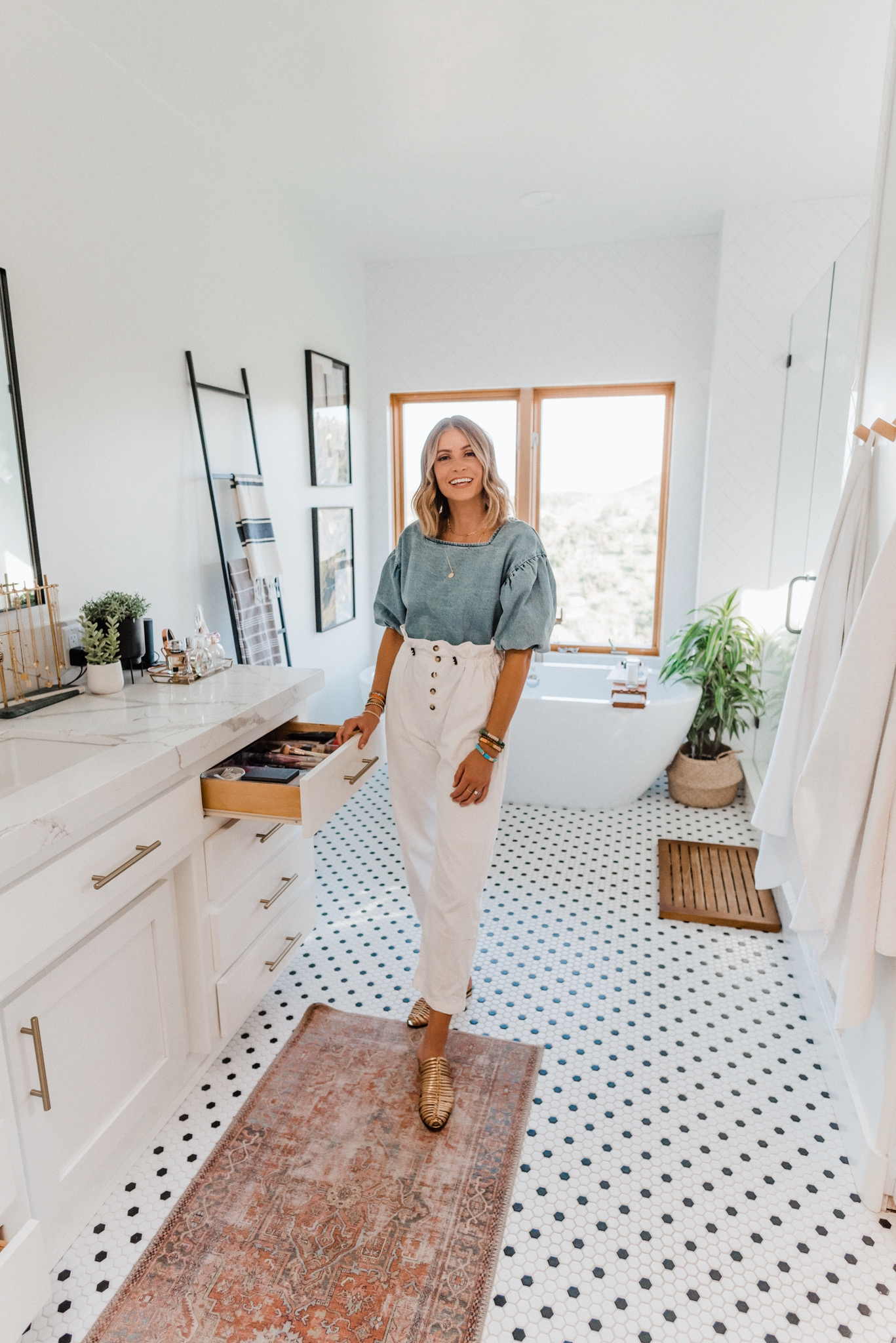 Kitchen Organization Products by popular San Diego life and style blog, Navy Grace: image of a woman wearing a THE ODELLS: EVERLY BUTTON BACK TOP, Urban Outfitters BDG Wisconsin Casual Ecru Pant, and Cecelia GLORIA mule and standing next to her open organized makeup drawer in her bathroom vanity.