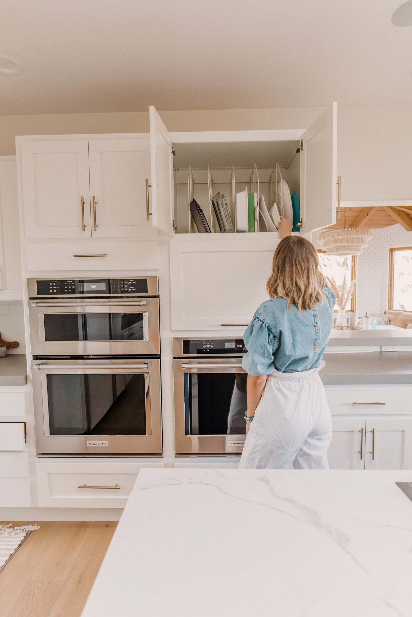 Kitchen Organization Products by popular San Diego life and style blog, Navy Grace: image of a woman wearing a THE ODELLS: EVERLY BUTTON BACK TOP, Urban Outfitters BDG Wisconsin Casual Ecru Pant, and Cecelia GLORIA mule while looking in a kitchen cupboard.