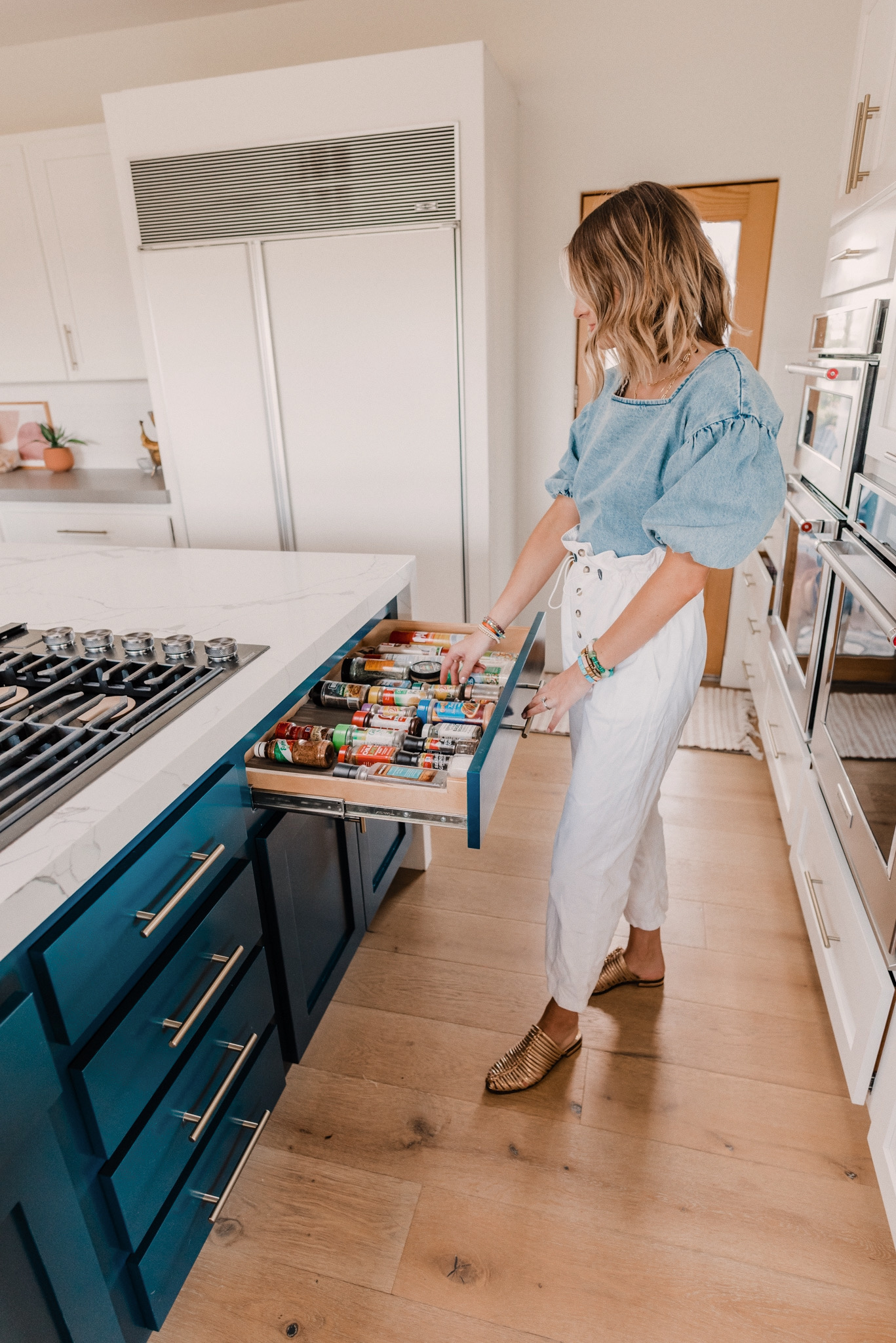 Kitchen Organization Products by popular San Diego life and style blog, Navy Grace: image of a woman wearing a THE ODELLS: EVERLY BUTTON BACK TOP, Urban Outfitters BDG Wisconsin Casual Ecru Pant, and Cecelia GLORIA mule while looking in her organized spice drawer.