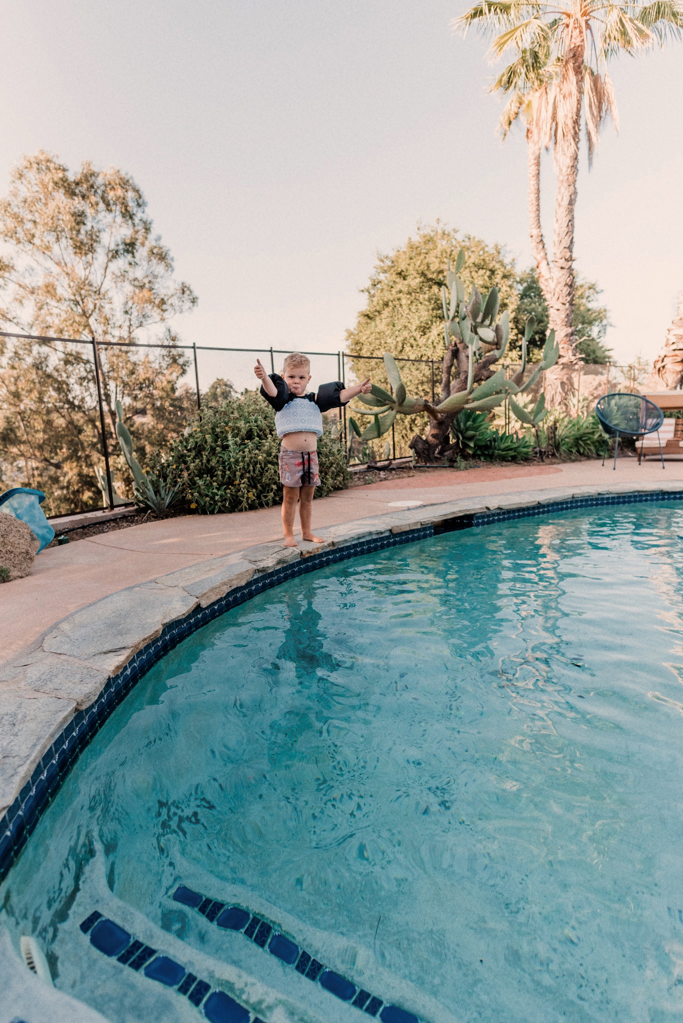 Kids Swimsuits by popular San Diego fashion blog, Navy Grace: image of a little boy giving two thumbs up as he wears a tiger print swimsuit, puddle jumper and stands on the edge of a swimming pool.