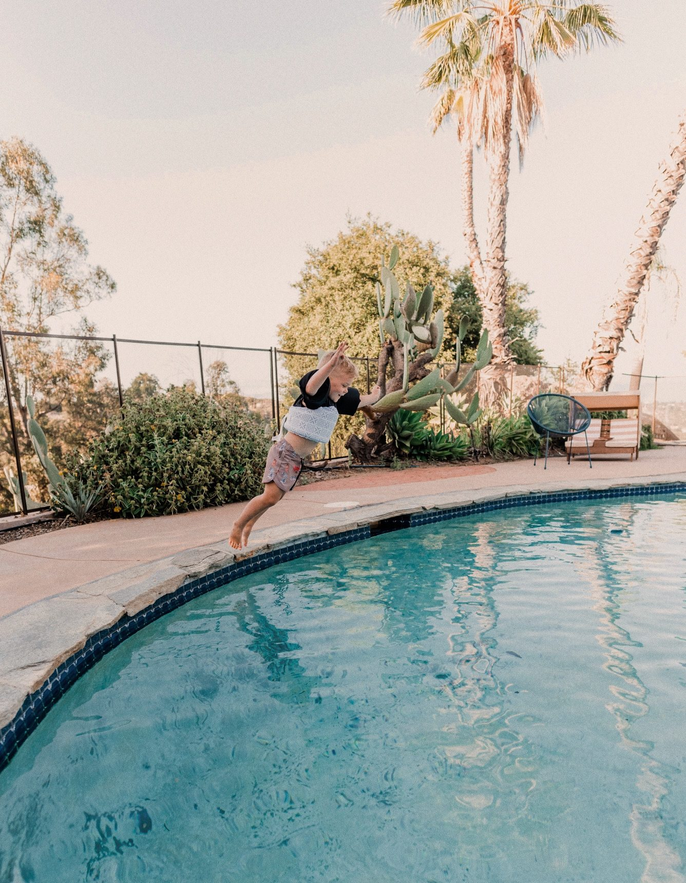 Kids Swimsuits by popular San Diego fashion blog, Navy Grace: image of a little boy wearing swimsuit and puddle jumper and jumping into a swimming pool.