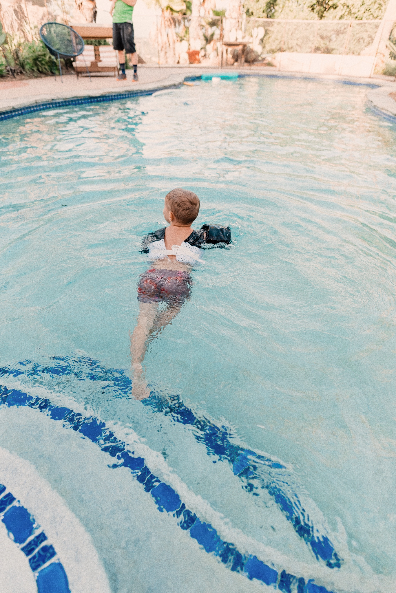 Kids Swimsuits by popular San Diego fashion blog, Navy Grace: image of a little boy wearing a tiger print swimsuit and puddle jumper as he swims in his swimming pool.