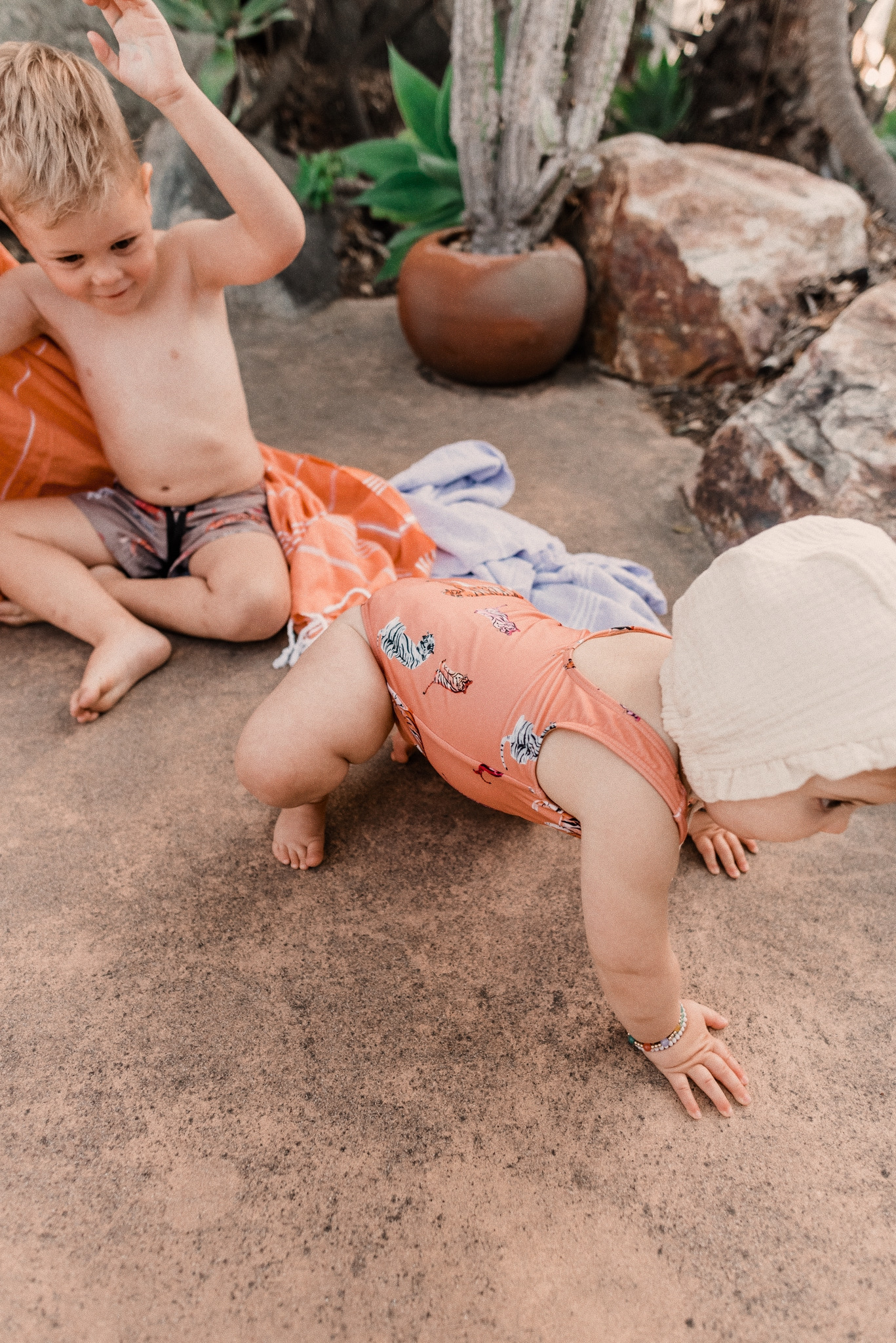 Kids Swimsuits by popular San Diego fashion blog, Navy Grace: image of a little boy wearing a tiger print swimsuit and a baby girl wearing a tiger print swimsuit and bonnet while they sit together on their Turkish towels.