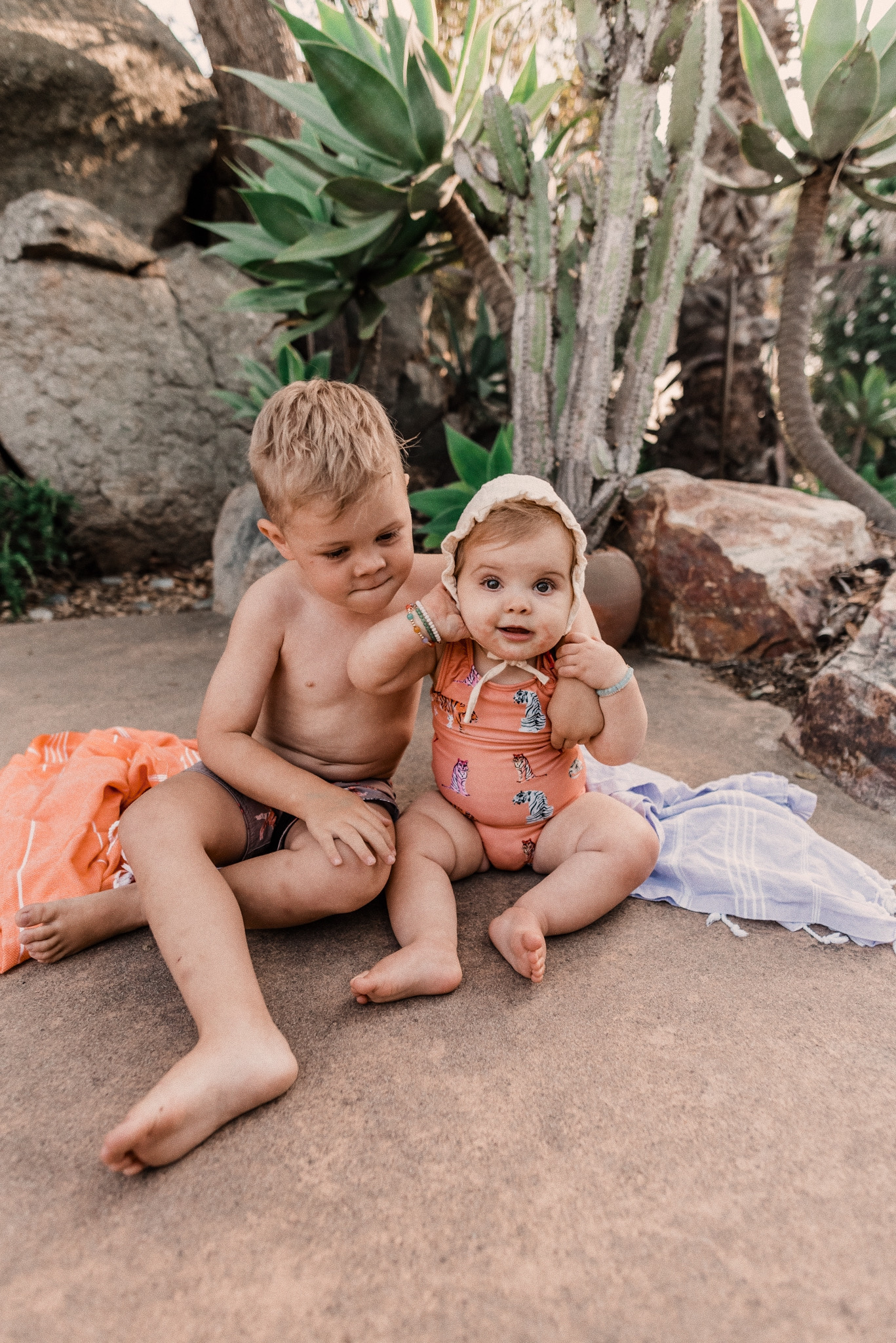 Kids Swimsuits by popular San Diego fashion blog, Navy Grace: image of two kids sitting together outside next to their Turkish towels and wearing swimsuits.
