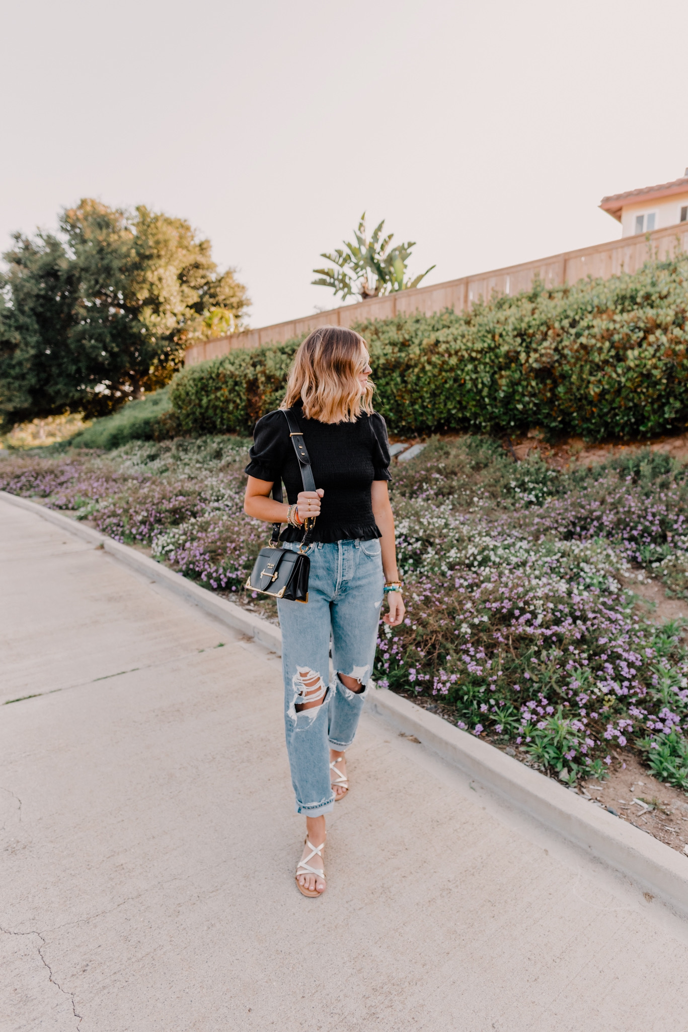 New Sale Favorites by popular San Diego fashion blog, Navy Grace: image of a woman walking outside and wearing a Forever 21 Smocked Ruffled Top, Revolve Agolde 90s Mid Rise Loose Fit jeans, H&M gold colored sandals, Farfetch PRADA Cashier shoulder bag, and Ray-Ban ROUND DOUBLE BRIDGE sunglasses.