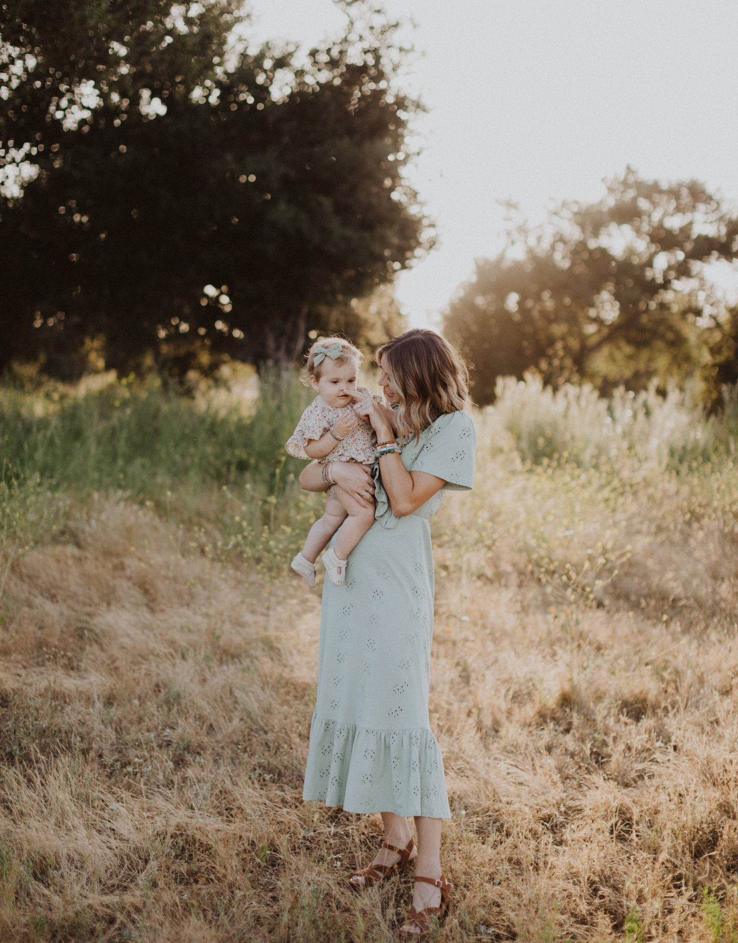 Life Update by popular lifestyle blog, Navy Grace: image of a baby girl wearing white mary jane shoes, a mint green bow head band, and a floral print dress and being held by her mom who is wearing a sage green eyelet dress.